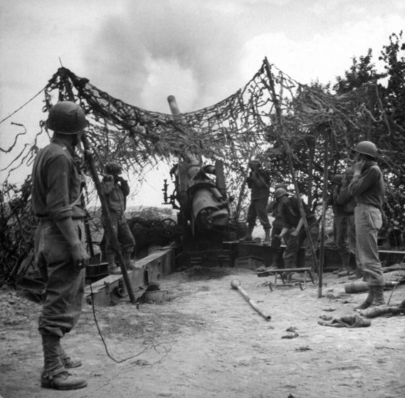 Camouflaged American artillery fires on German positions during Allied campaign in North Africa during WWII.