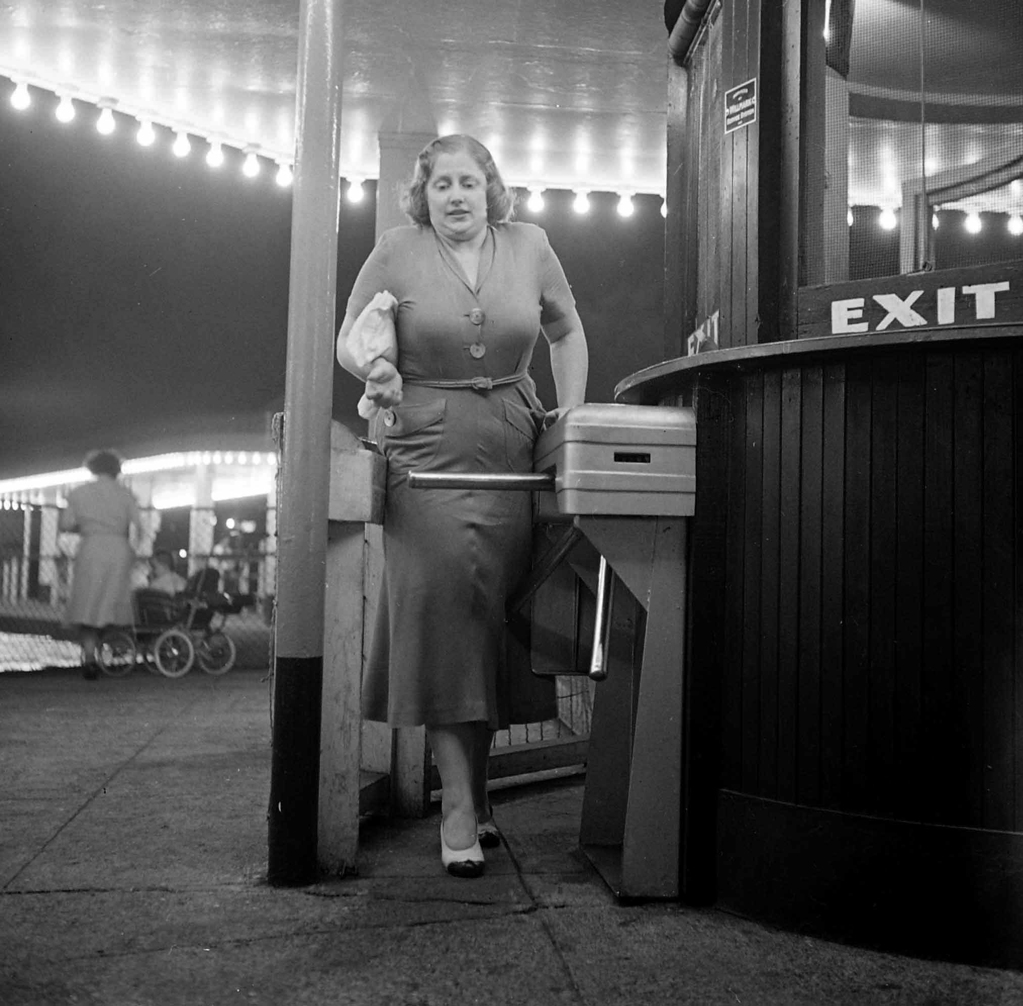 Dorothy Bradley, photographed for LIFE magazine article on obesity, squeezes through turnstile, 1949.