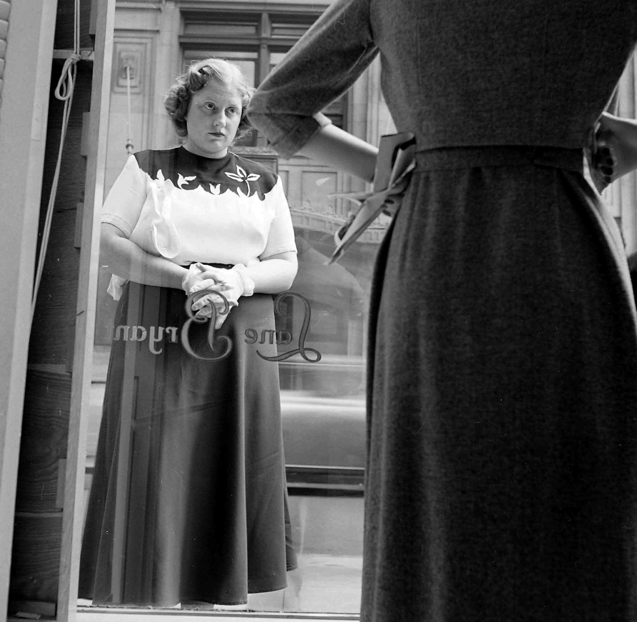 Dorothy Bradley, photographed for LIFE magazine article on obesity, eyes dress in a store window, 1949.