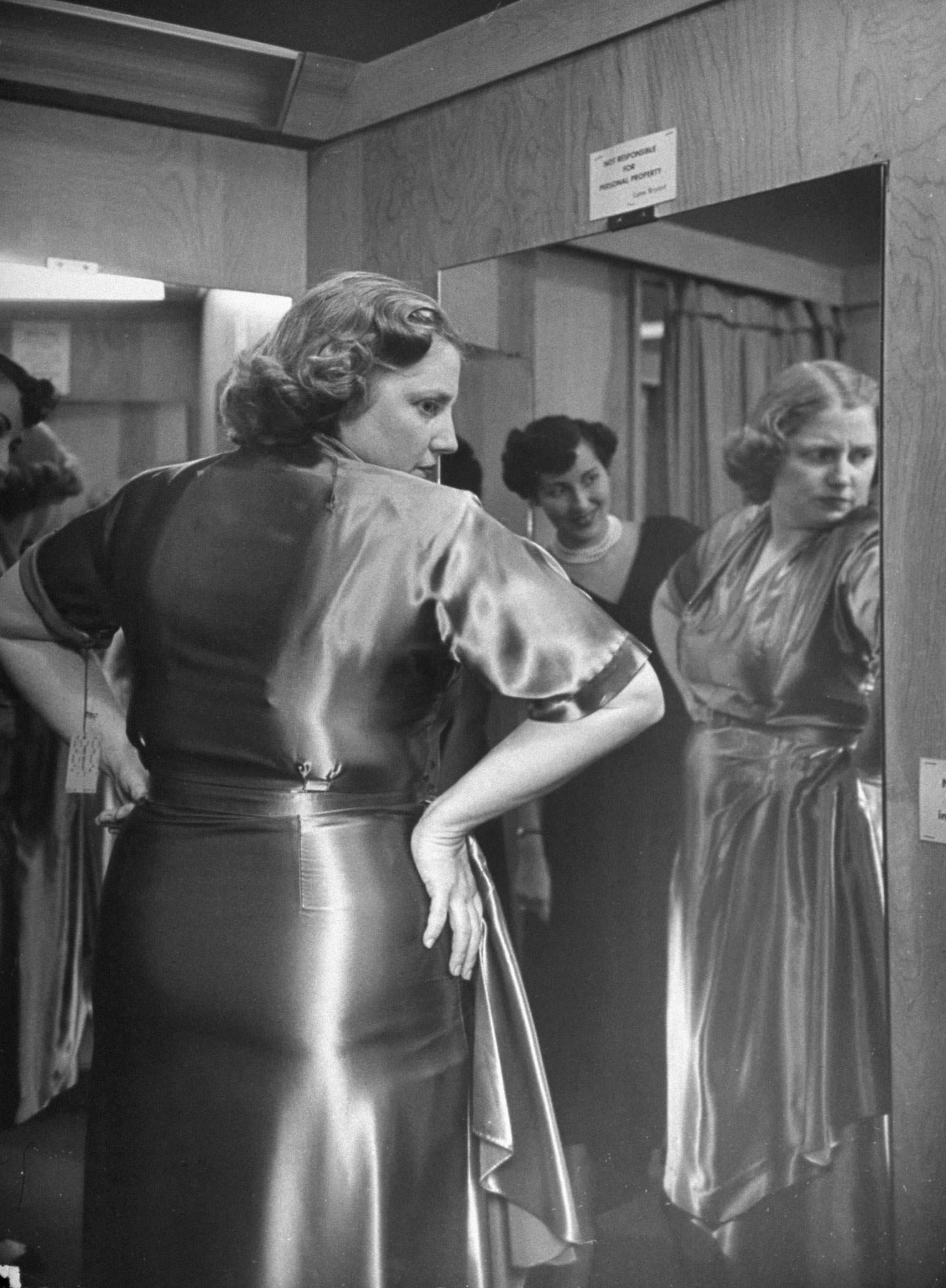 <b>Caption from LIFE.</b> Embarrassed at shop because she wears a size 40, Dorothy tries on new dress. A friend encouragingly points out that dieting has reduced waistline by two sizes