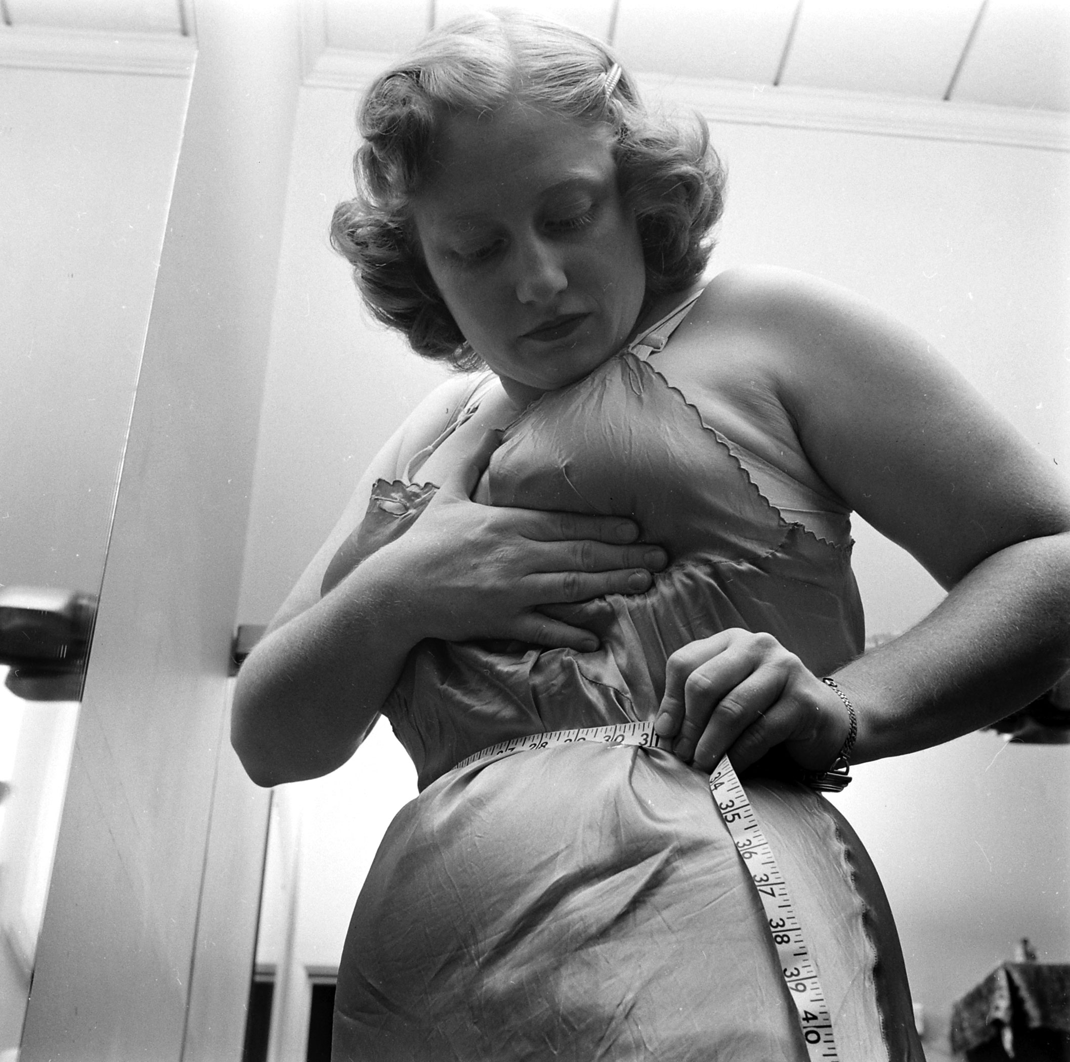 Dorothy Bradley, photographed for LIFE magazine article on obesity, measures her waist, 1949.