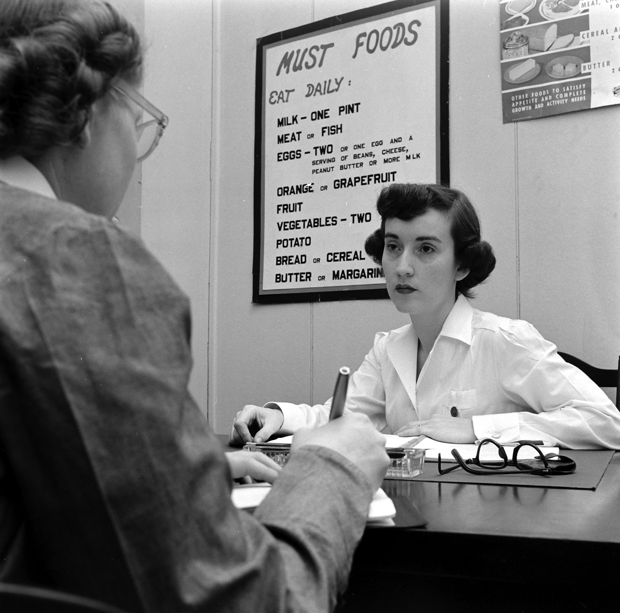 Dorothy Bradley (left), photographed for LIFE magazine article on obesity, meets with a nutritionist, 1949.