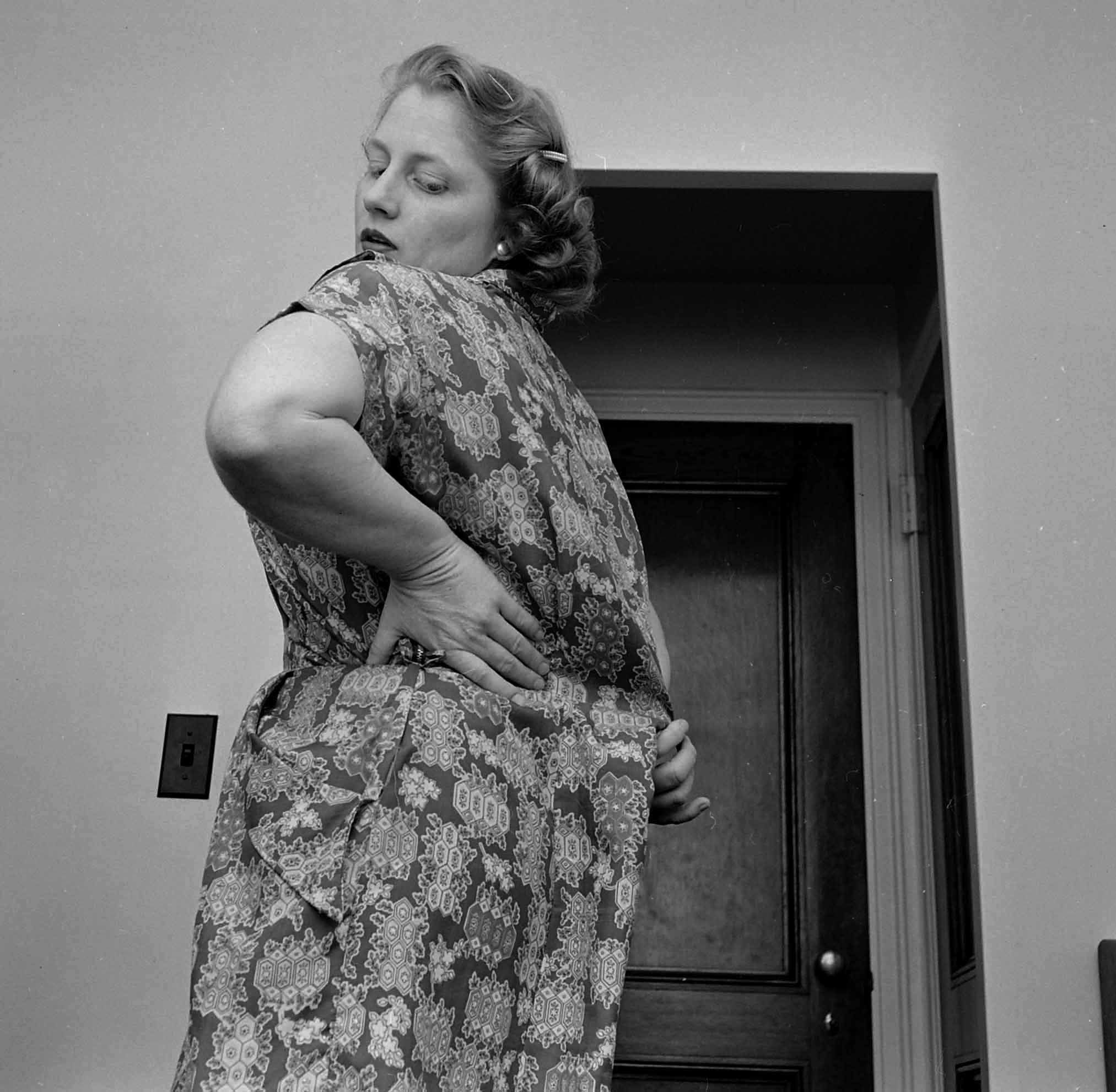 Dorothy Bradley, photographed for LIFE magazine article on obesity, tries on a dress, 1949.