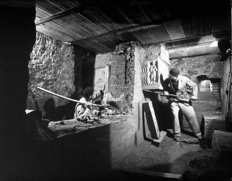 Workmen examining underneath the floor of Basilico.