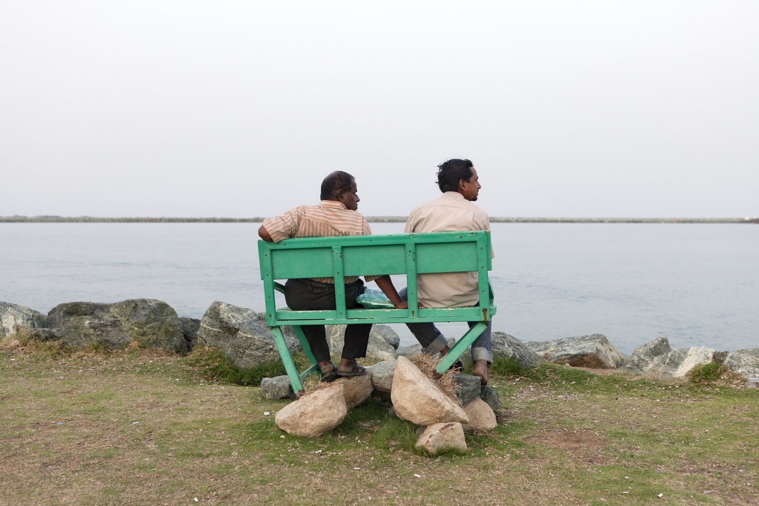 Men relax on a bench at the corniche in Fujairah.