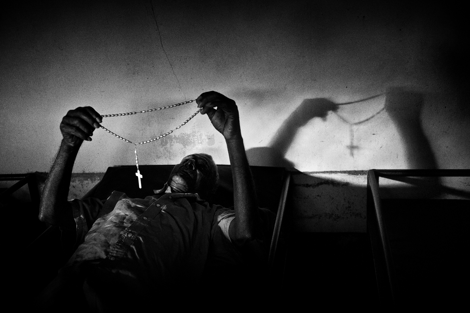 A patient suffering from suspected of mental illness prays on his bunk in Cochin, Kerala.                               In the state, three religions coexist peacefully: 55% Hindu, 25% Muslim and 20% Catholic. August 2009.