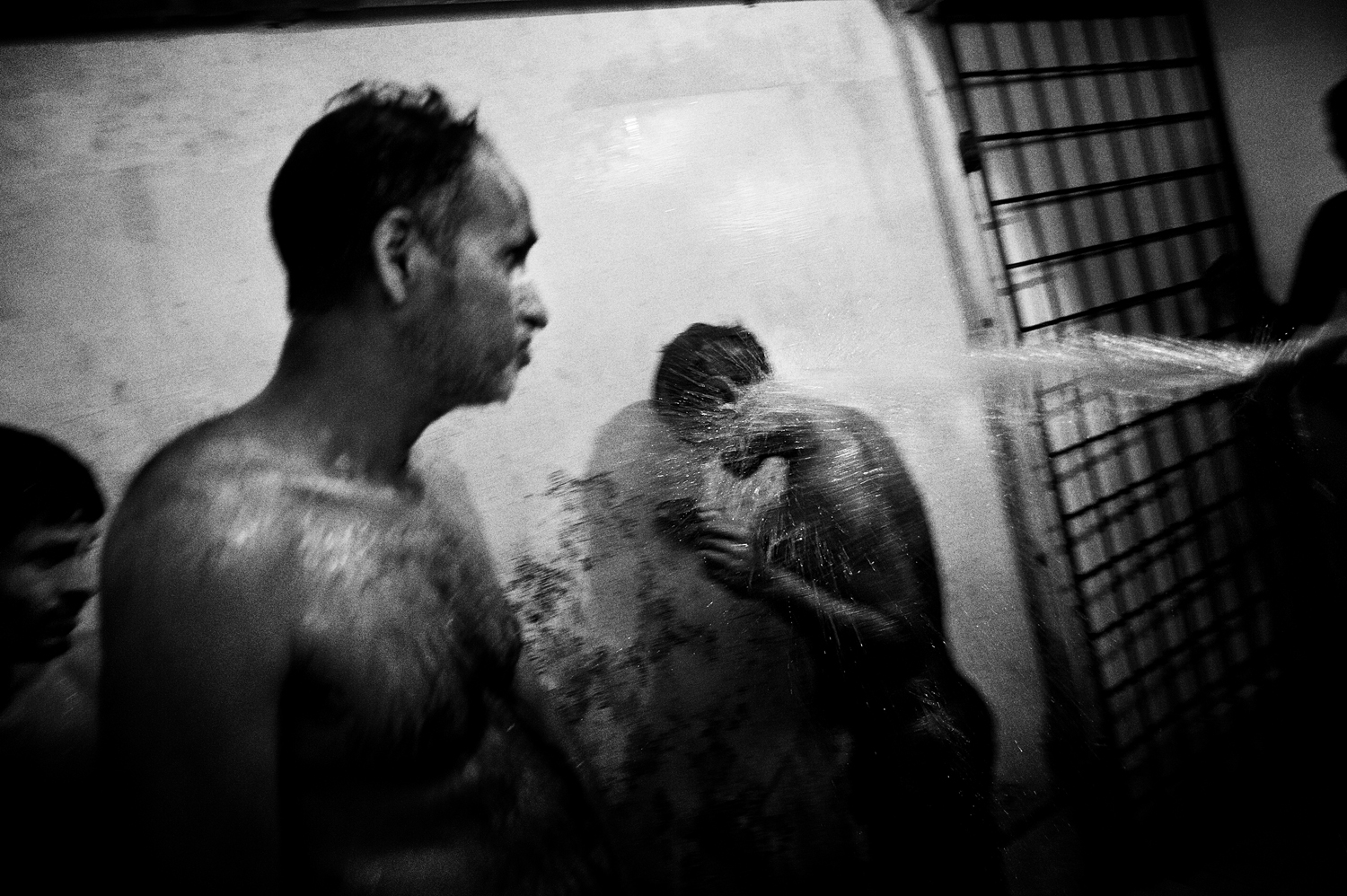 Patients suffering from suspected mental illness in the showers at a center run by volunteers in Thodupuzha, Kerala. August 2009.