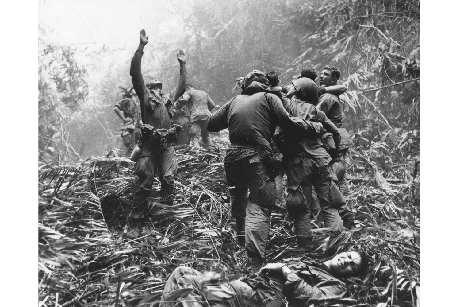 As fellow troopers aid wounded buddies, a paratrooper of A Company, 101st Airborne, guides a medical evacuation helicopter through the jungle foliage to pick up casualties during a five-day patrol of an area southwest of Hue, South Vietnam, April 1968. This photograph is featured on the cover of the Associated Press' new book 'Vietnam: The Real War' (Abrams, Oct. 2013).