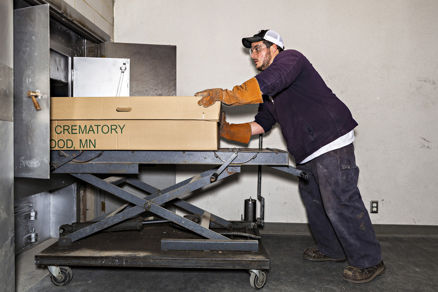 Roy Quinn, crematory operator at Forest Lawn Memorial, places a body into their fire-based cremation oven.