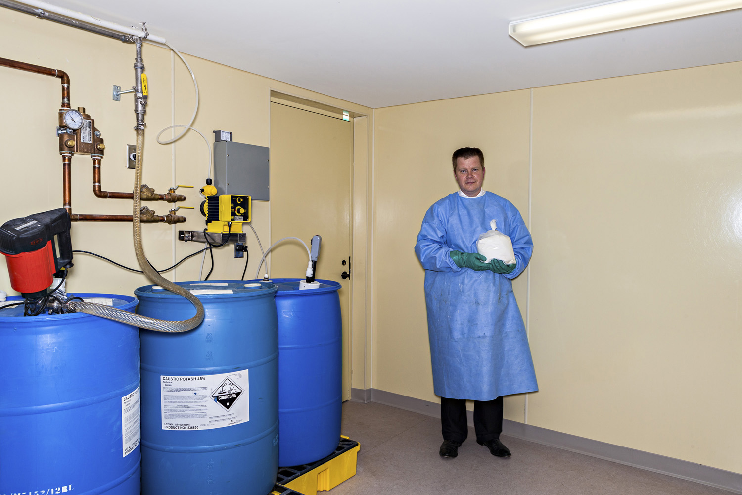 Jason Bradshaw poses next to barrels of chemicals used in the green cremation process, while holding a bag of human remains that have undergone this process.