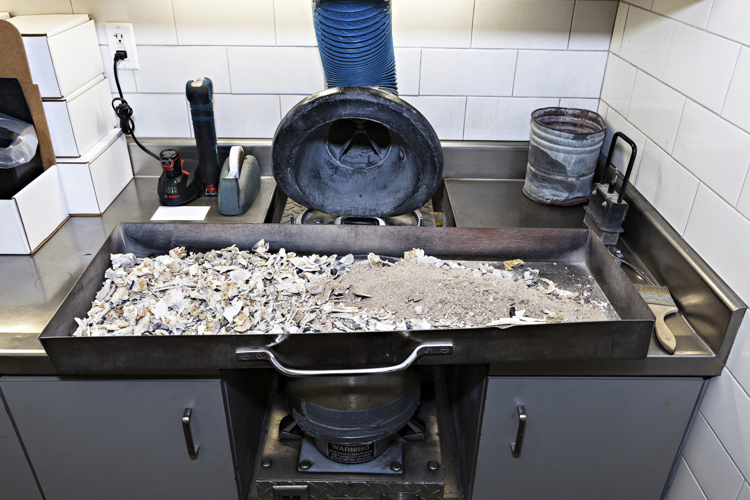 Fire-based cremation leaves behind ash but also substantial bone fragments, like those shown in this pan. These remains will be pulverized by the machine seen here beneath the pan before being returned to the family.