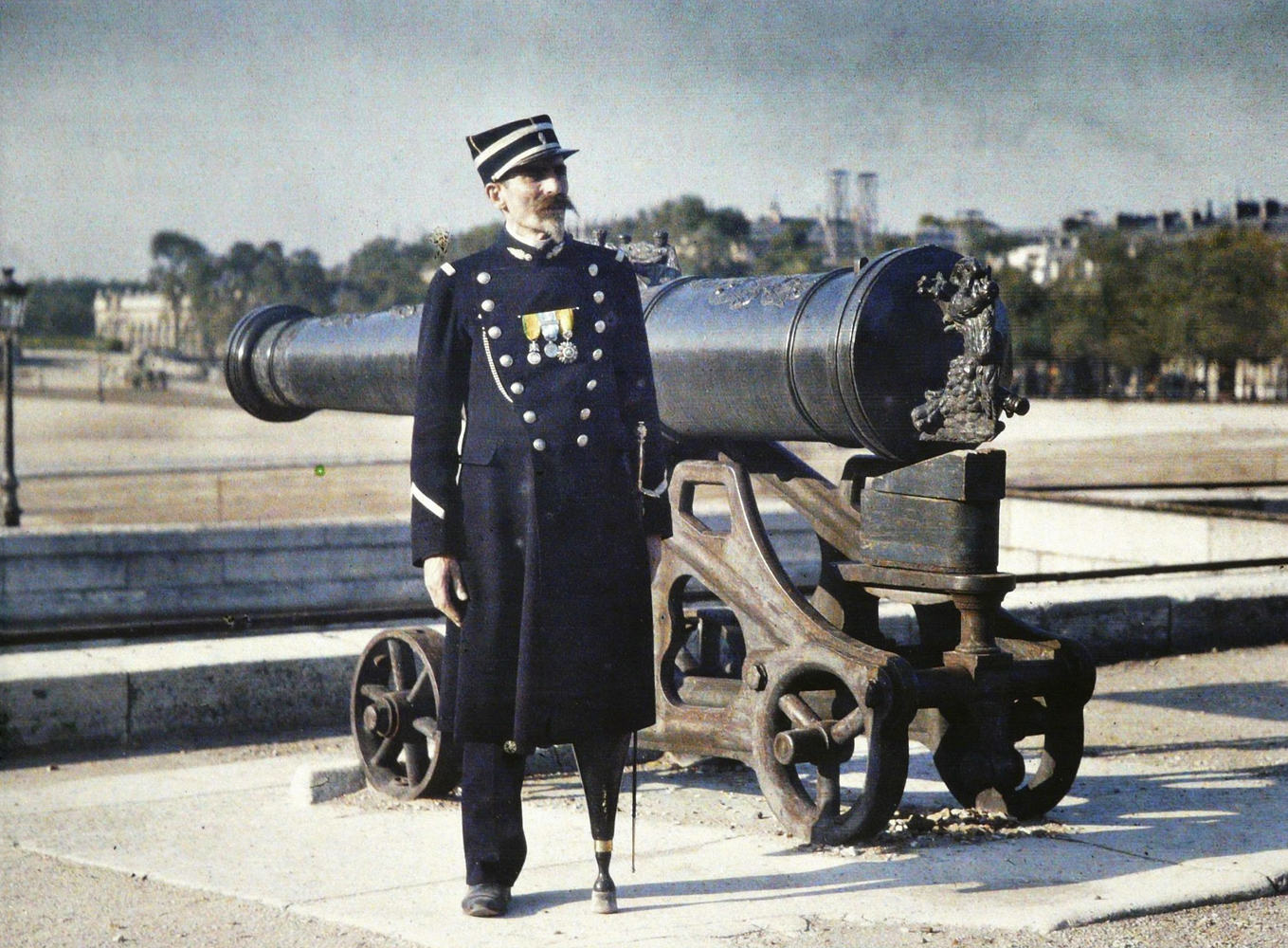 A soldier in uniform with three medals stands next to a cannon in Paris in 1918. His left leg has been replaced by an artificial limb.