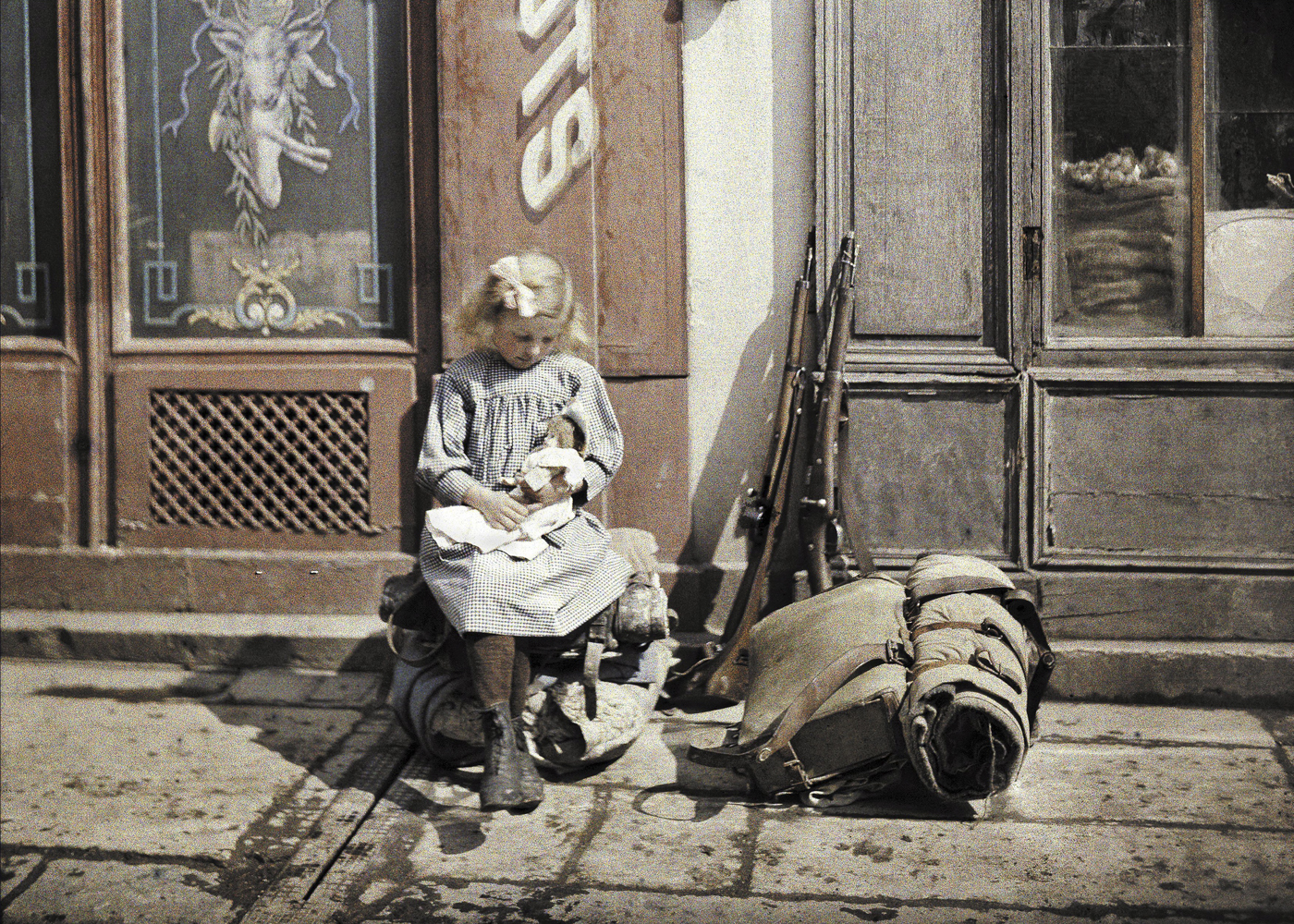 A little girl plays with her doll in Reims, France in 1917. Two guns and a knapsack are next to her on the ground.