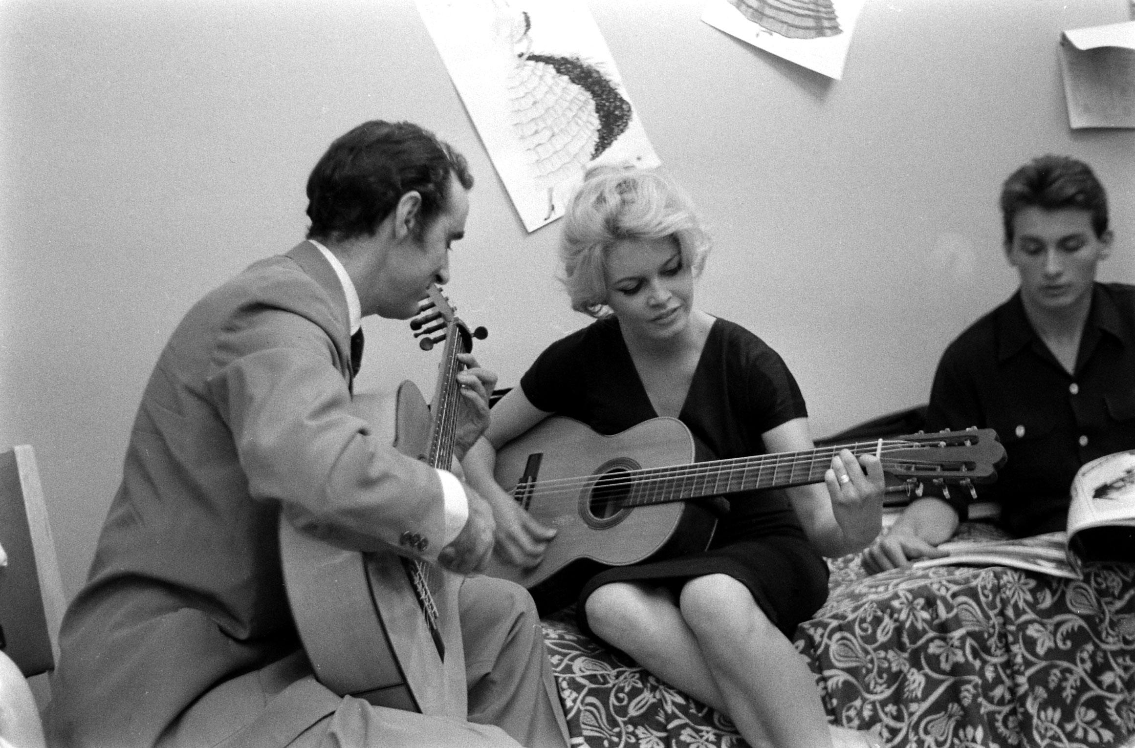 Brigitte Bardot plays the guitar while on the set of the film, <i>La Femme et le Pantin</i>, Spain, 1958.