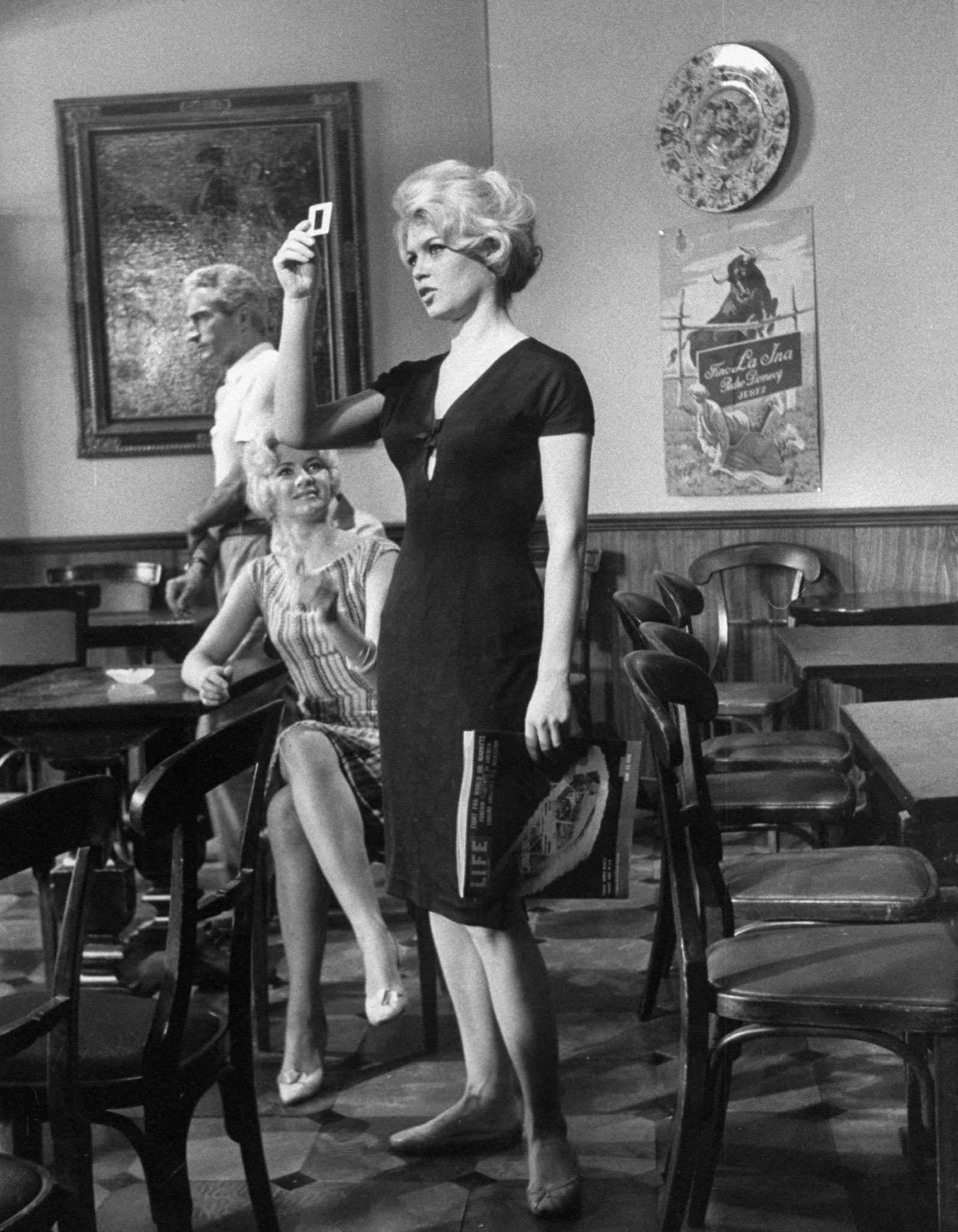 Brigitte Bardot (holding a copy of LIFE magazine) looks at a photographic slide on the set of the film, <i>La Femme et le Pantin</i>, Spain, 1958.