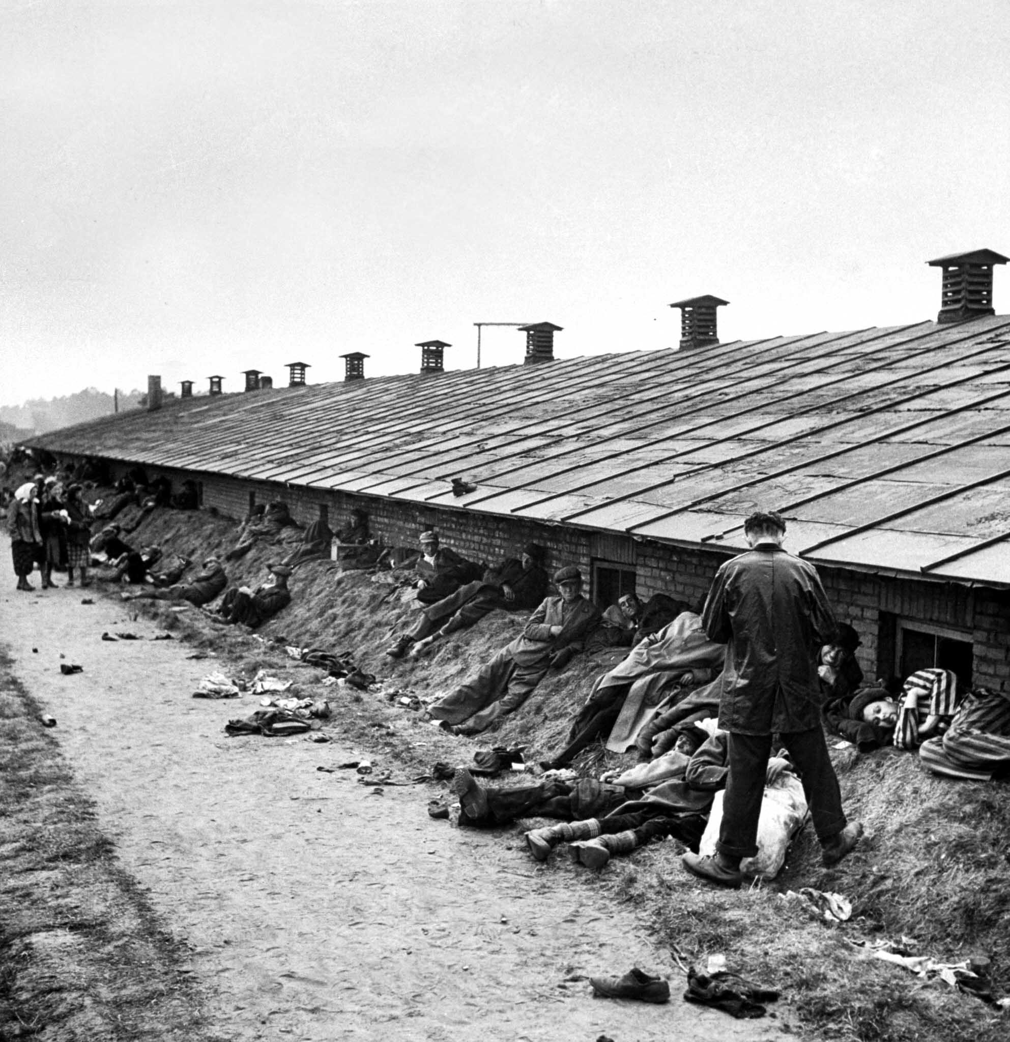 Dying men stretch out on a dirt bank behind one of the Bergen-Belsen barracks, 1945.