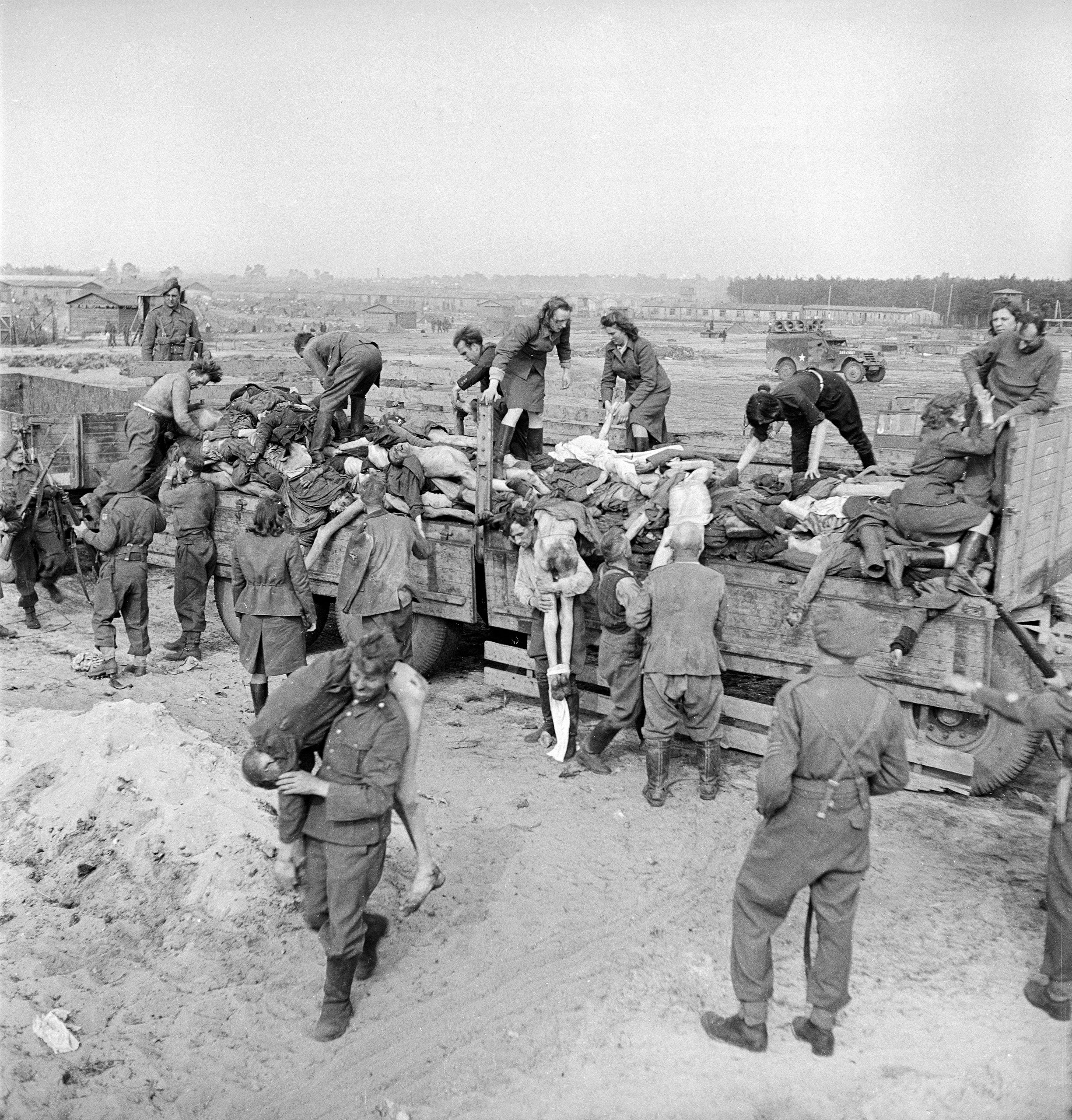 Male and female German SS soldiers forced to load corpses onto trucks under British guard at the Bergen-Belsen concentration camp, 1945.