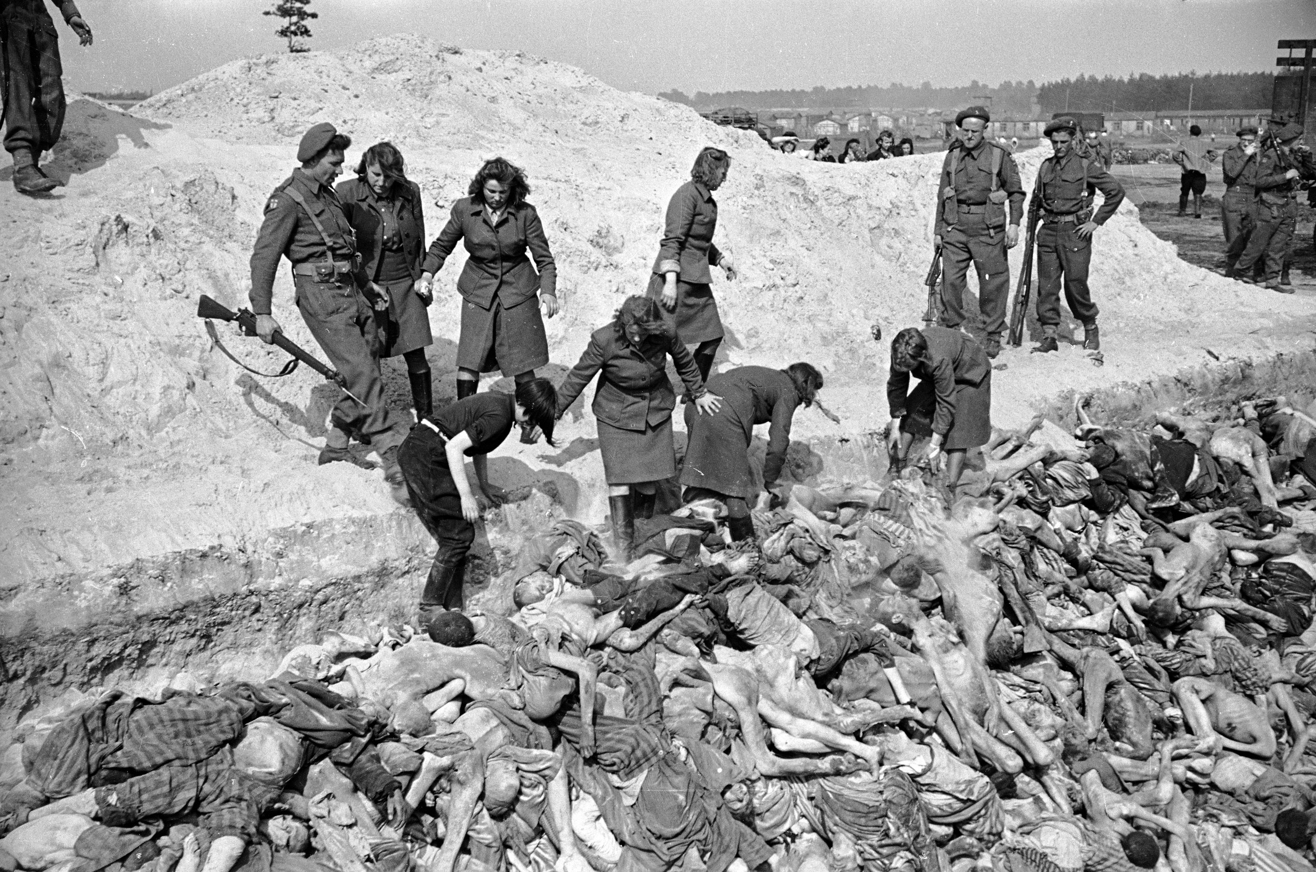 Female SS soldiers fill a mass grave with corpses while under guard by British soldiers at the Bergen-Belsen concentration camp, 1945.