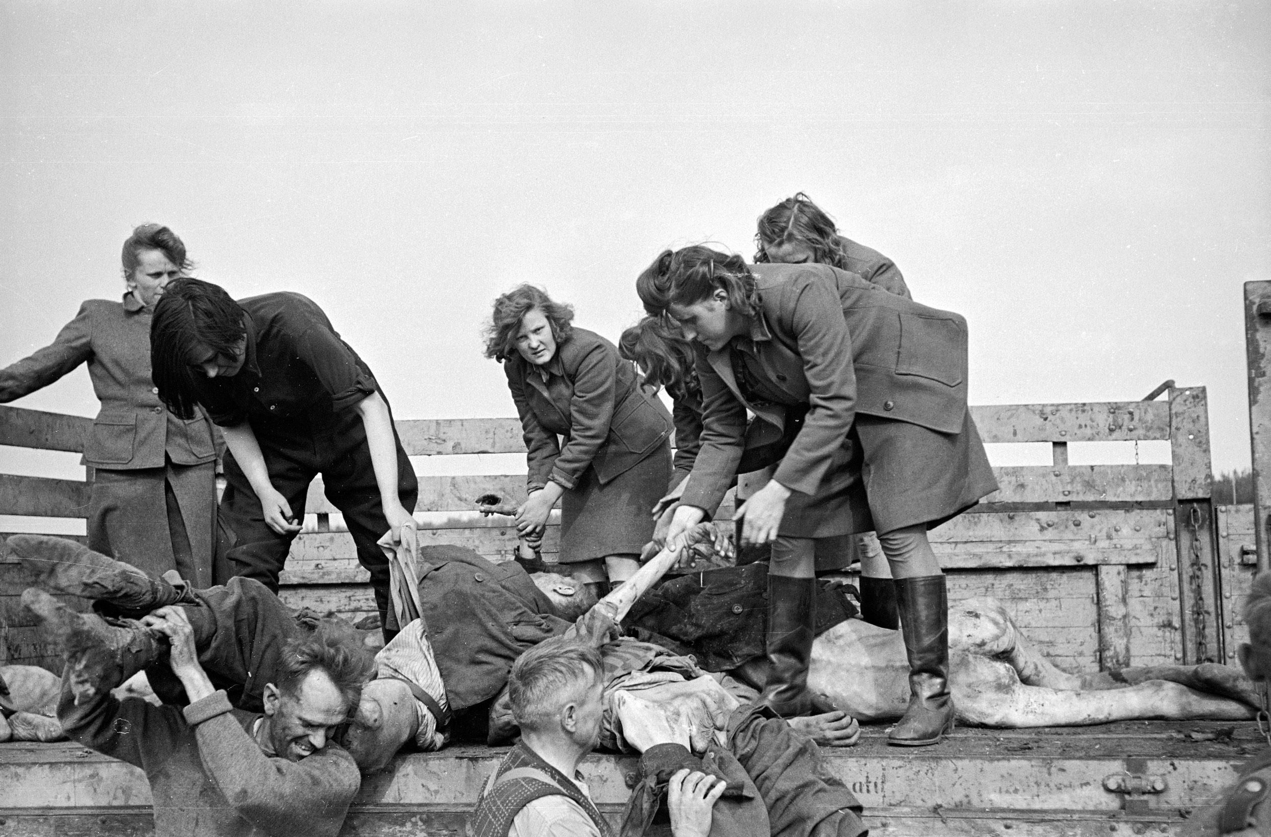 Female German camp guards unload a truck full of bodies of dead prisoners at Bergen-Belsen, April 1945.