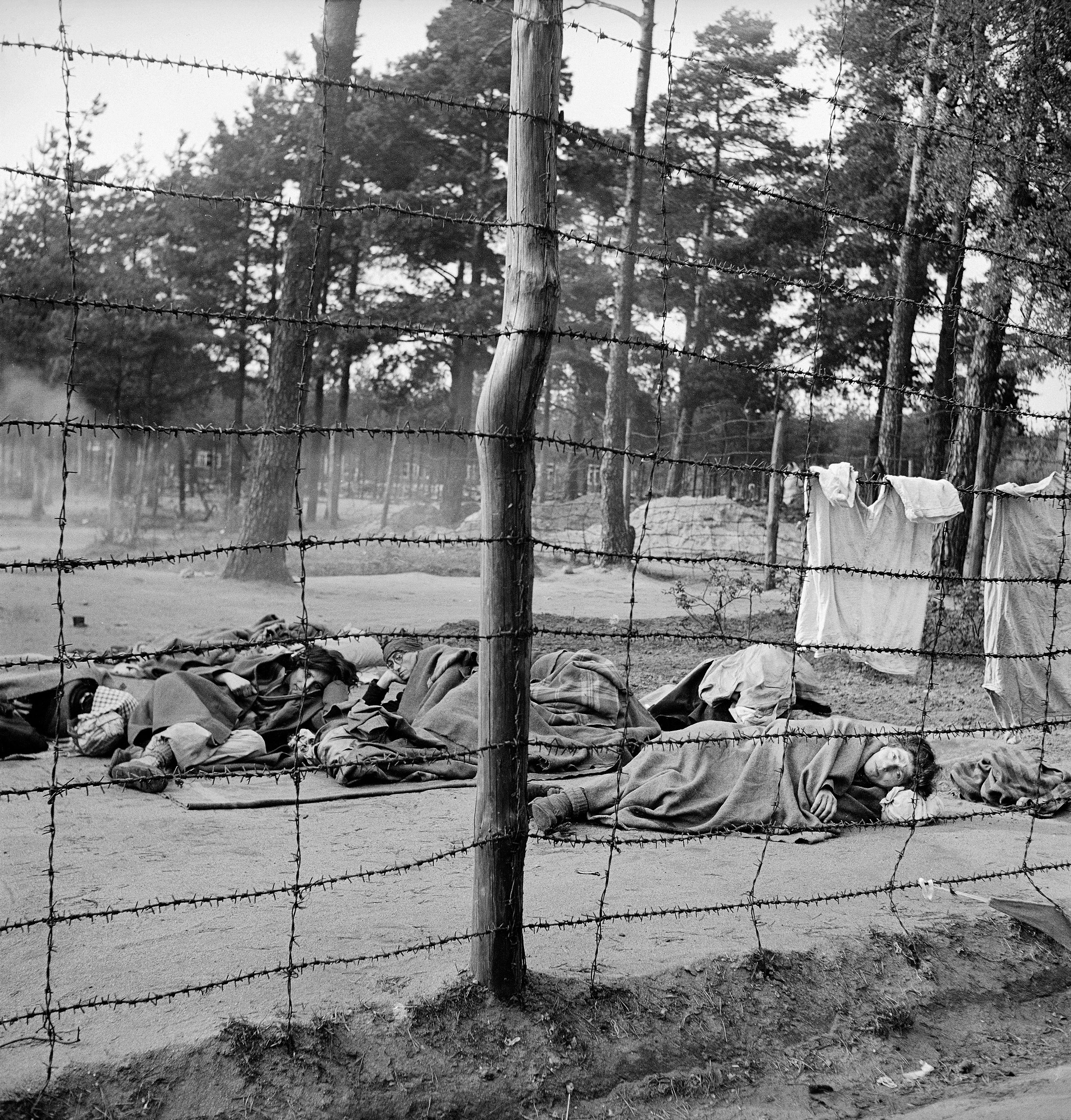 Dying women huddle on the ground behind the barbed-wire enclosure at Bergen-Belsen, 1945.