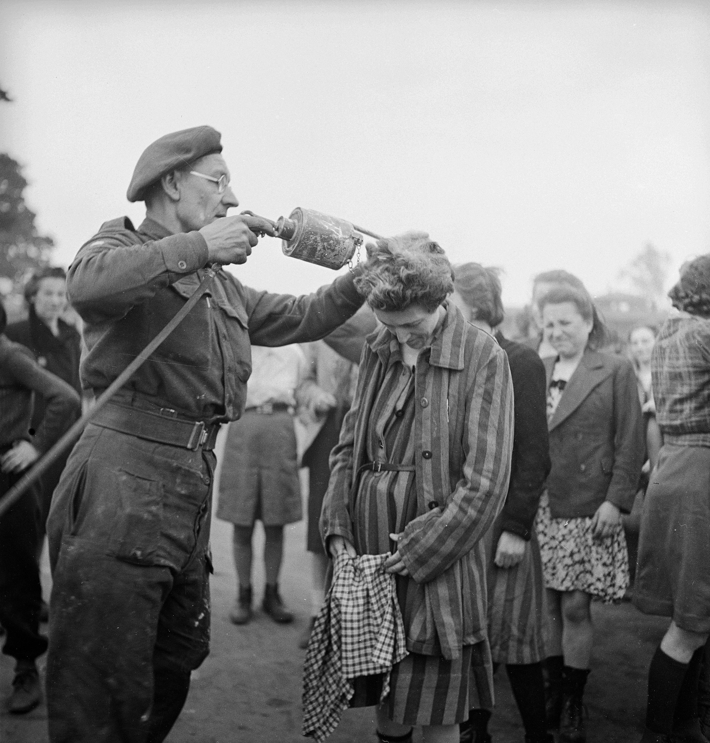 A British doctor uses DDT while delousing newly freed female prisoners at the Bergen-Belsen concentration camp, 1945.