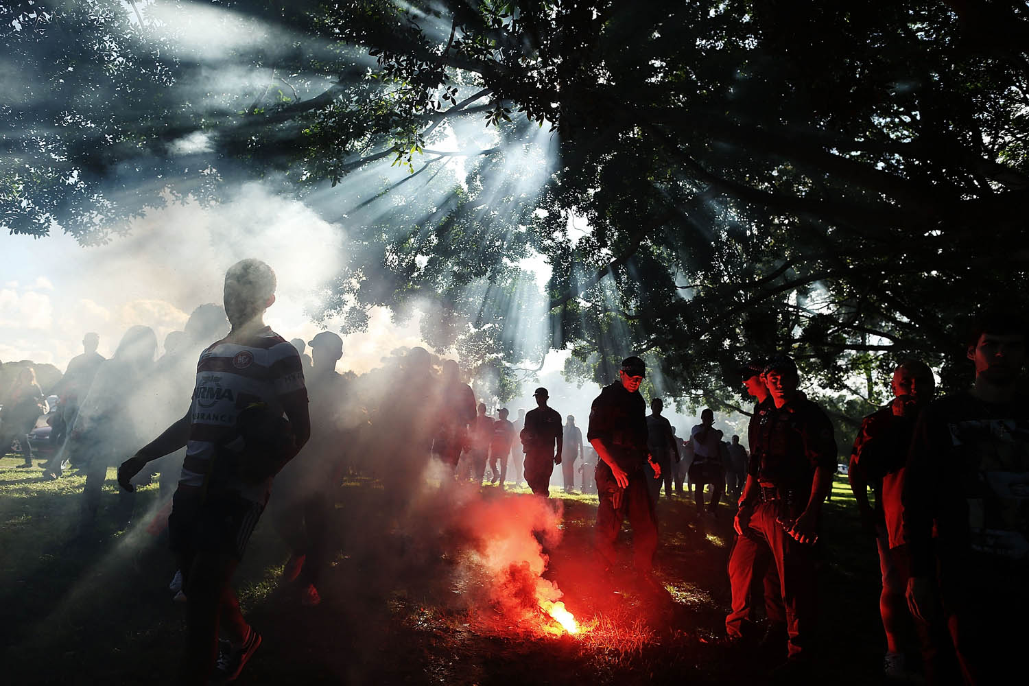 April 21, 2013. Police officers extinguish a flare as Western Sydney Wanderers fans walk to the stadium before the A-League 2013 Grand Final match between the Western Sydney Wanderers and the Central Coast Mariners at Allianz Stadium in Sydney.