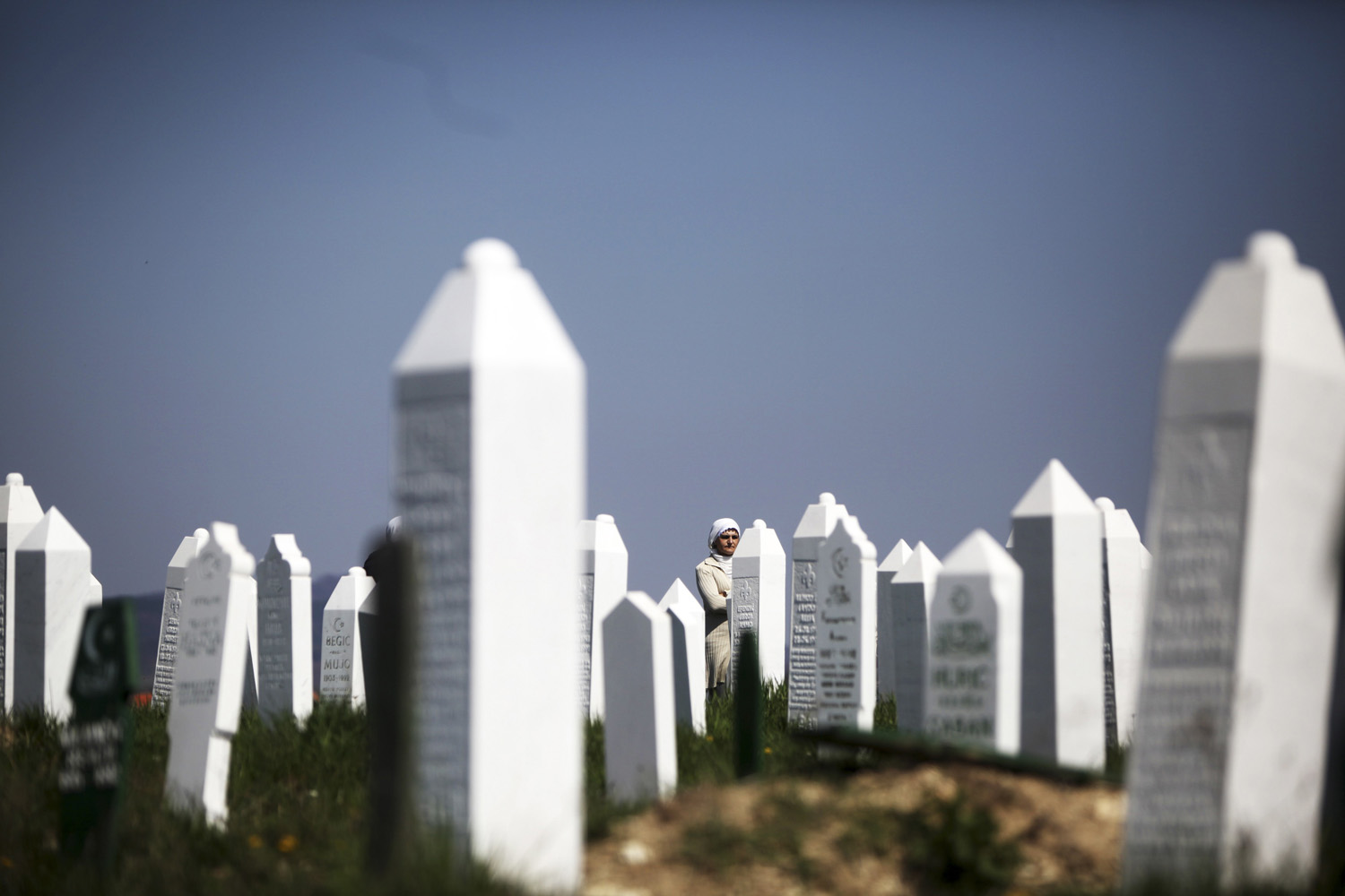 April 20, 2013. Bosnian Muslim women stand near graves before a mass funeral in the town of Vlasenica, in the Serbian part of Bosnia. The remains of some 11 Bosnian Muslims, killed by Serb forces during the country's 1992-1995 Bosnian war, were exhumed from mass graves near Vlasenica with more expected to be found.