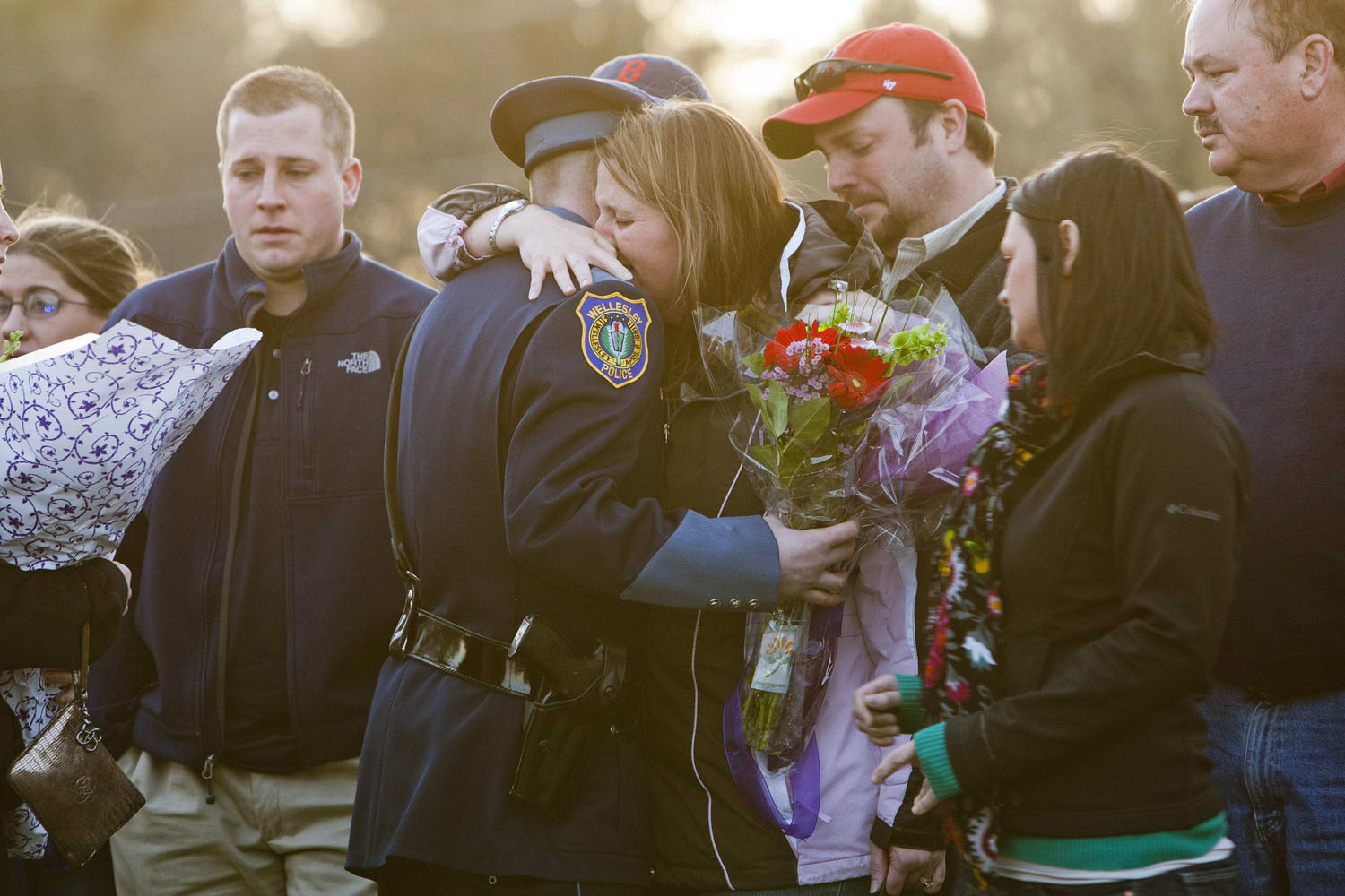 April 20, 2013. Nicole Collier Lynch, sister of slain MIT police officer Sean Collier, hugs a Wellesley police officer during a vigil at the Town Common in Wilmington, Massachusetts. Collier, 26, was shot multiple times in his car on as Boston Marathon bombing suspects Dzhokhar Tsarnaev and his brother Tamerlan tried to evade capture.