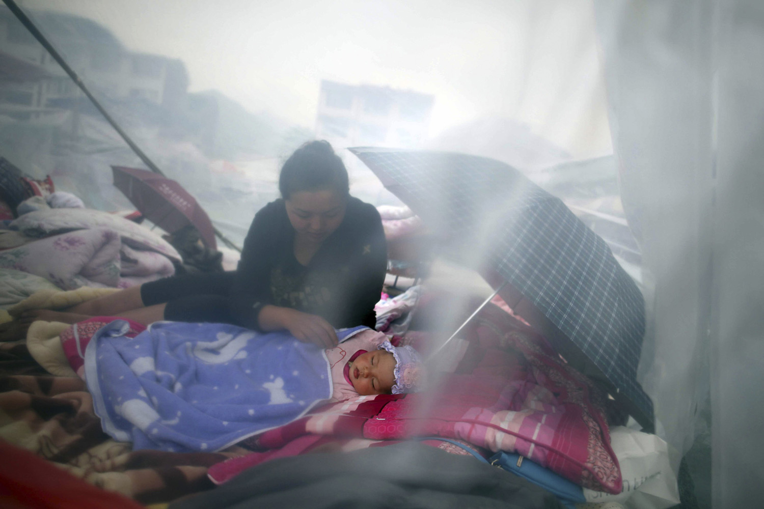April 21, 2013. A woman looks at her child as they rest among the wreckage after an earthquake in Lingguan town of Baoxing county, Sichuan province.