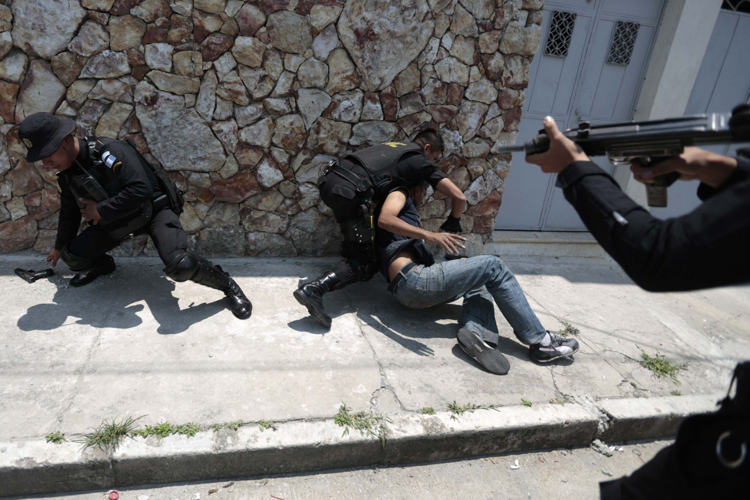 April 22, 2013. Police officers capture a suspected hit man after the murder of a bus driver in Zona 6 in Guatemala City.