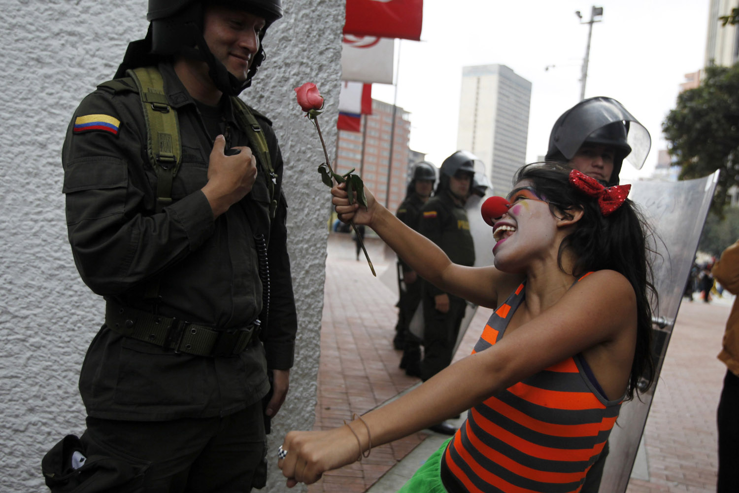 April 22, 2013. A student gestures with a flower to a policeman as she marches during the closing ceremony of the  Congress for Peace  in Bogota.