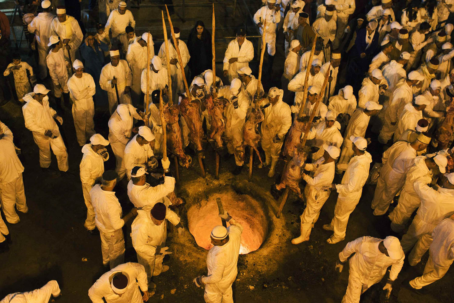 April 23, 2013. Members of the Samaritan sect place large sheep skewers into an oven during a traditional Passover sacrifice ceremony on Mount Gerizim, near the West Bank city of Nablus.