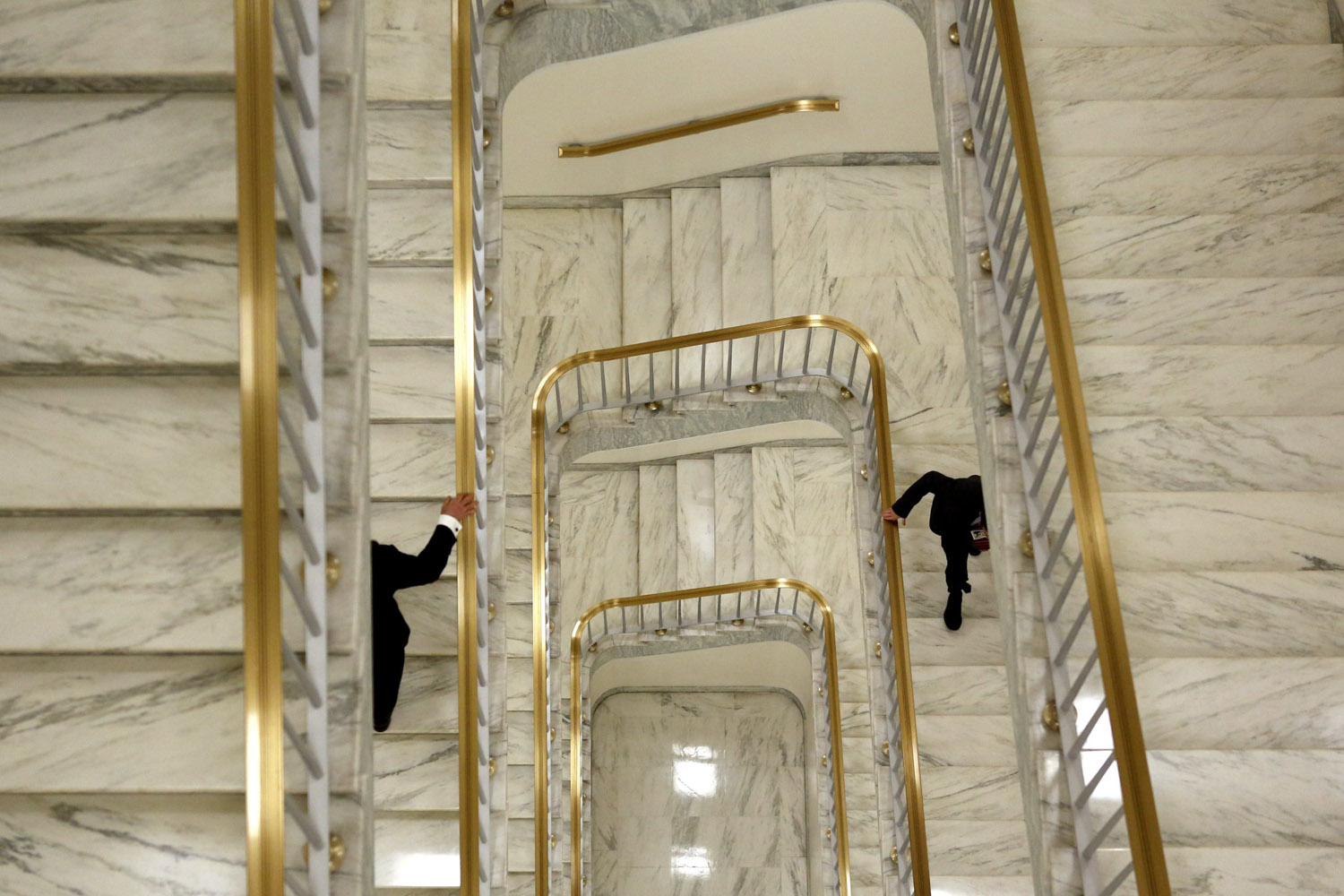 April 24, 2013.Two men hold onto the banister as they ascend a staircase in the Rayburn House Office Building on Capitol Hill in Washington.