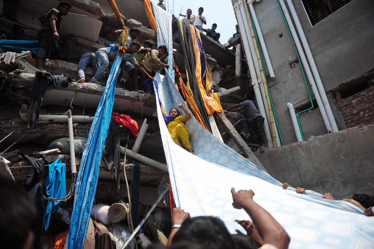 April 24, 2013. Bangladeshi garment workers help evacuate a survivor using lengths of textile as a slide to evacuate from the rubble after an eight-storey building collapsed in Savar, on the outskirts of Dhaka.