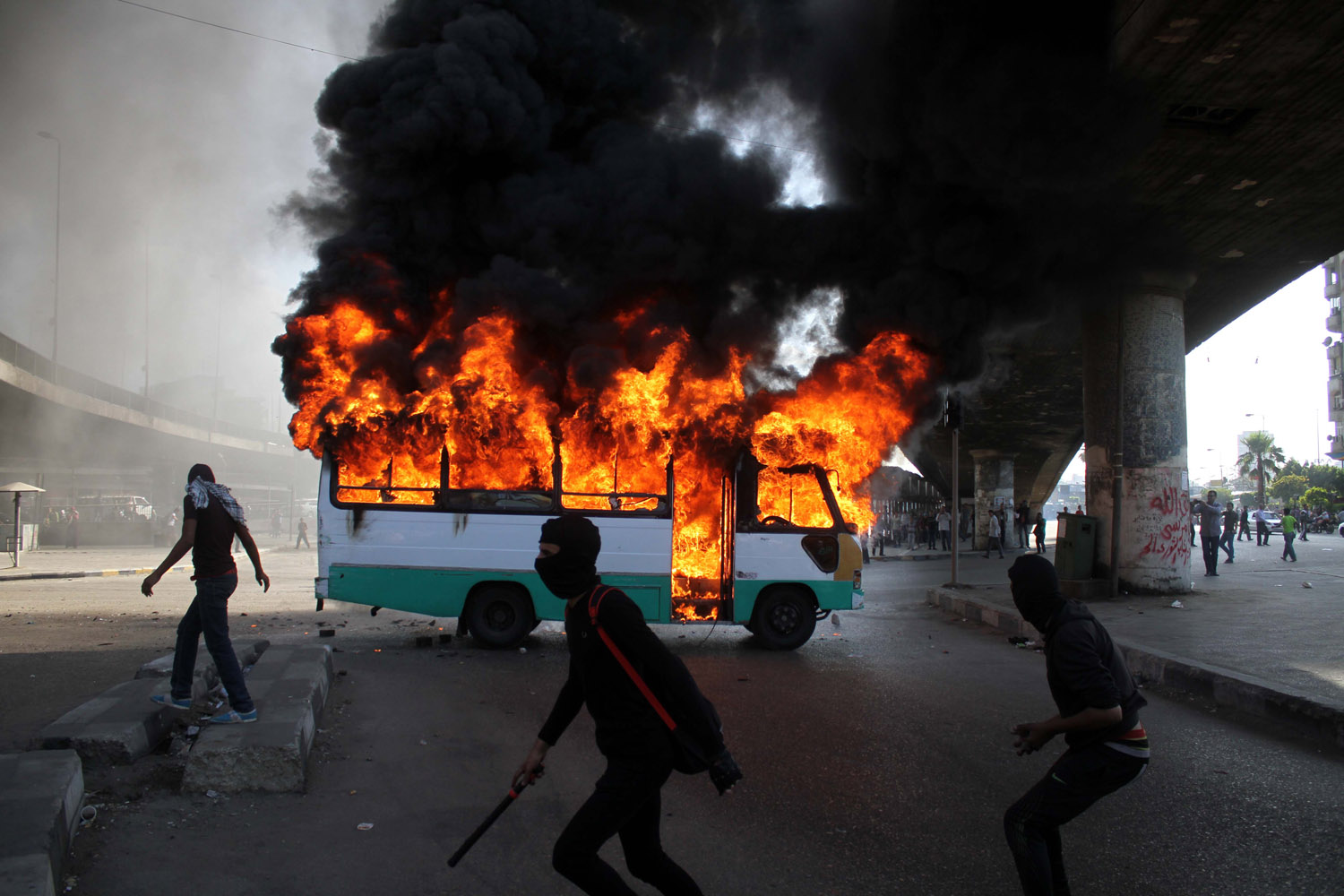 April 19, 2013. Egyptian protesters clash near a bus belonging to Muslim Brotherhood supporters burns after it was reportedly set alight by anti-government protesters in Cairo. Clashes erupted between several hundred opponents and supporters of Egyptís Islamist president during a rally by his allies, calling on him to  cleanse the judiciary  of alleged supporters of the old regime.