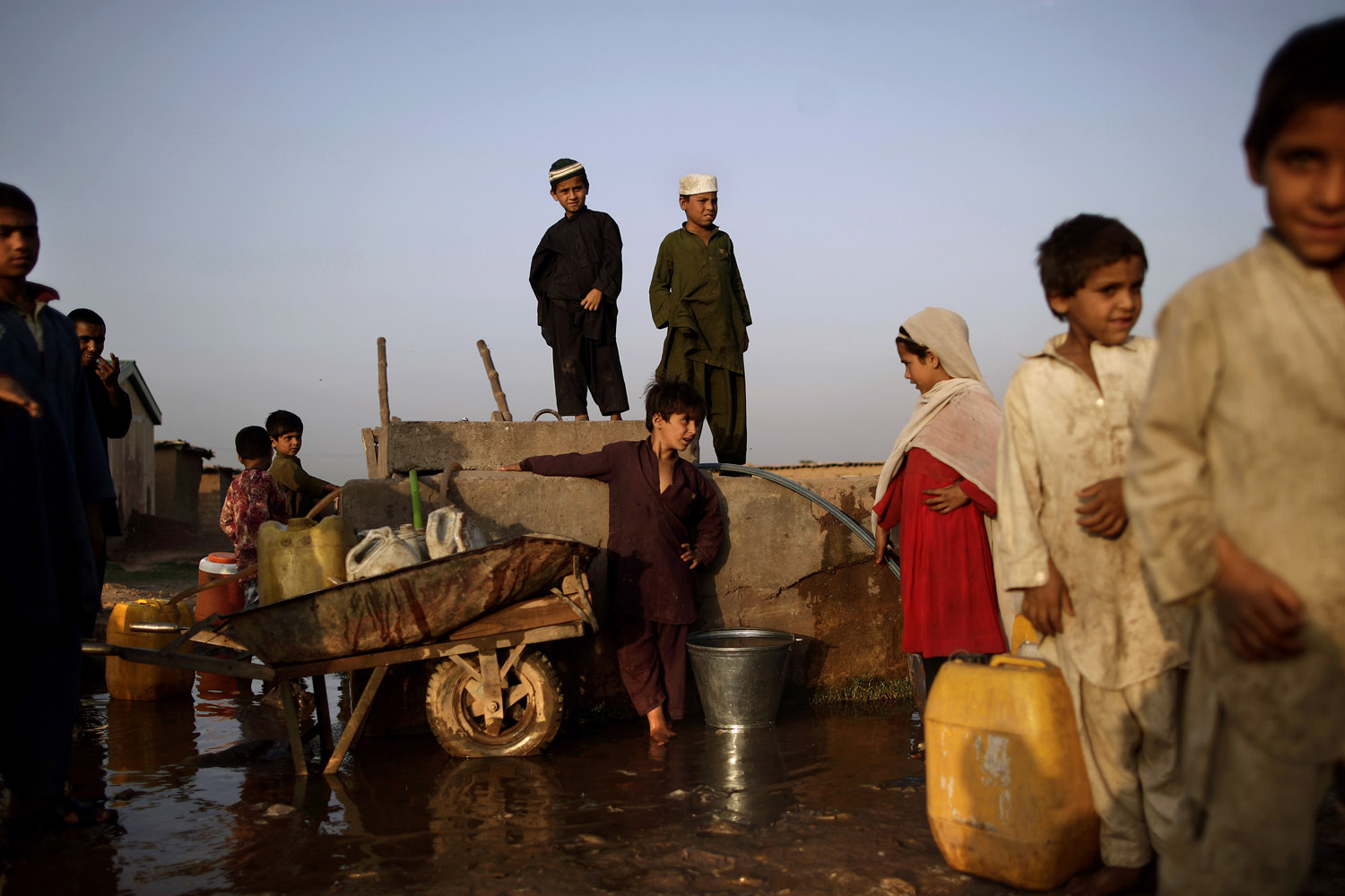 April 22, 2013. Afghan refugee children collect water from a water point on the outskirts of Islamabad.