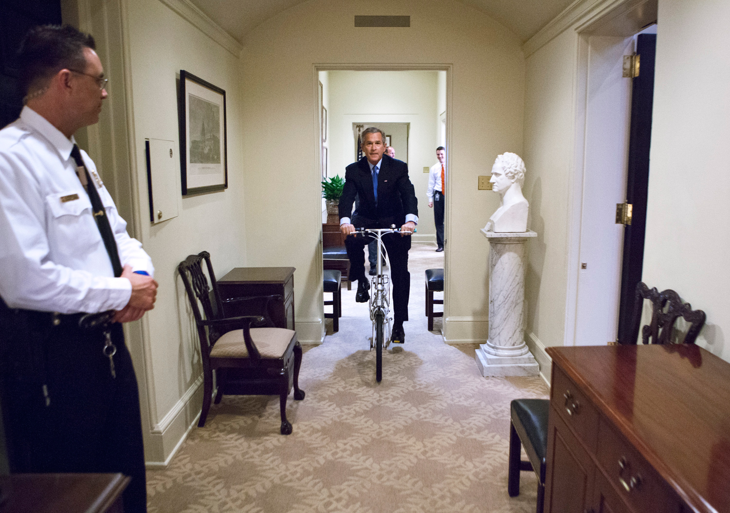 "July 12, 2005. President Bush enjoys a break in his afternoon schedule as he rides a fold-up bike, given by Prime Minister Lee Hsien Loong of Singapore.""He unfolded a bike out of a box -- a gift from the Prime Minister of Singapore -- and took it for a spin in the Oval Office and the hallway. It was funny watching a nearby Secret Service Agent try to keep a straight face with the President riding by."""
