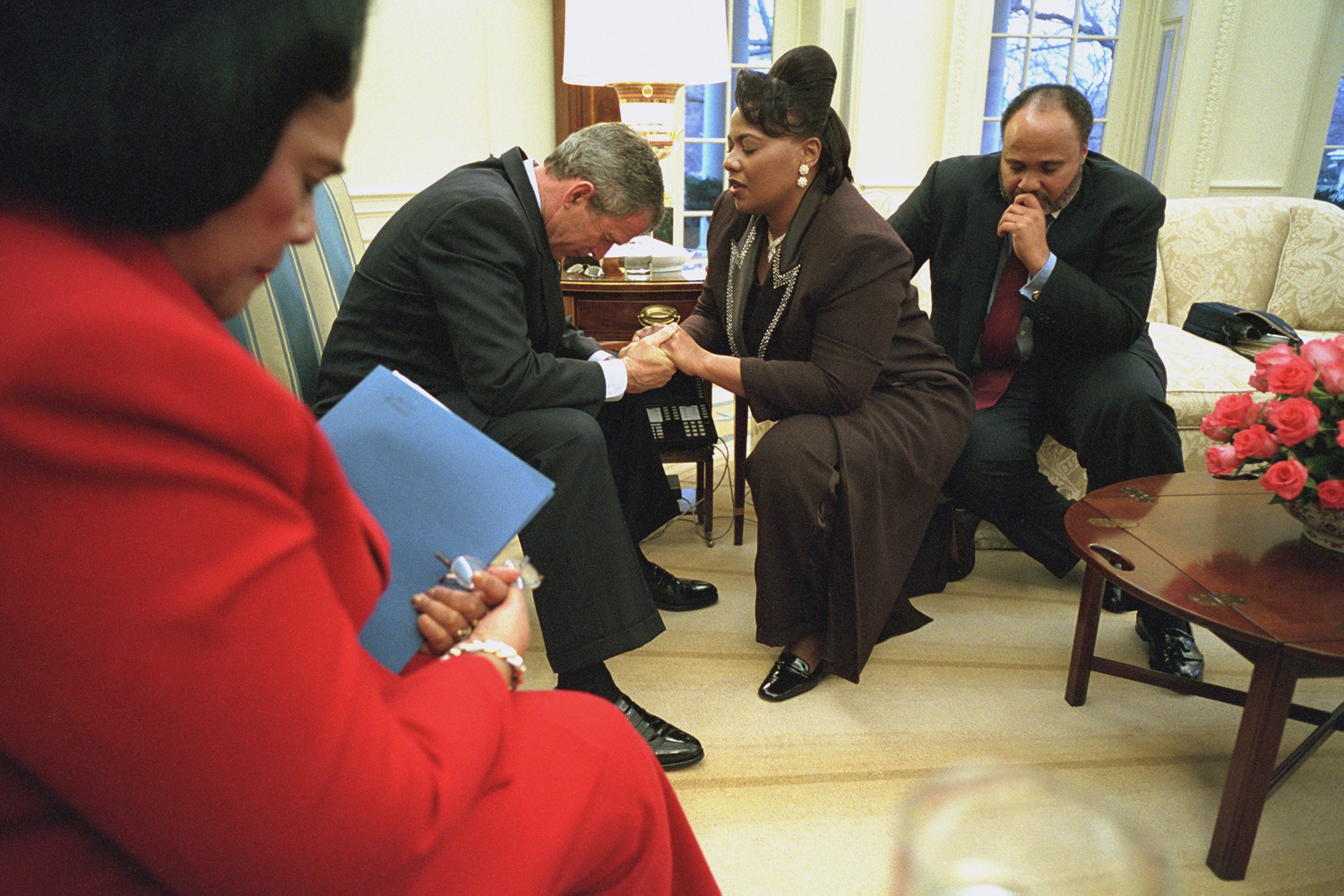 "July 27, 2006. Coretta Scott King, left, holds the plans for the Martin Luther King Memorial in her arms as President Bush joins in prayer with Bernice King and Martin Luther King III during their visit to the Oval Office.""Coretta Scott King asked the president to pray with them and he did. It was touching to see how instantly intimate they were, joining hands to pray. After the meeting, I escorted Coretta Scott King down to the library where her husband's bust was and she asked me to photograph her. It was such an honor."""