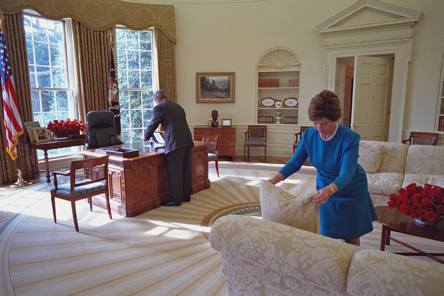 "Jan. 30, 2002. President and Mrs. Bush make some last-minute adjustments as they prepare to welcome decorators and donors to the Oval Office.""The President and Mrs. Bush were truly a team and greatly respected each other,  Draper says.  They were also playful, teasing each other and making each other laugh."""