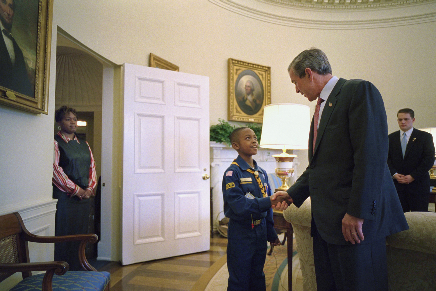 "Feb. 12, 2002. President Bush shakes hands with nine-year-old Cub Scout Jordon Wade of Pittsburgh, Pennsylvania, as he welcomes him to the Oval Office for the presentation of the Boy Scouts of America report to the Nation. Jordon's mother, Monica Jackson, looks on. ""It was a tender, sweet moment. The little boy seemed very respectful of the president, but shy. It was his big moment. The president made him comfortable with a warm, direct look. He had a way of doing that with visitors."""