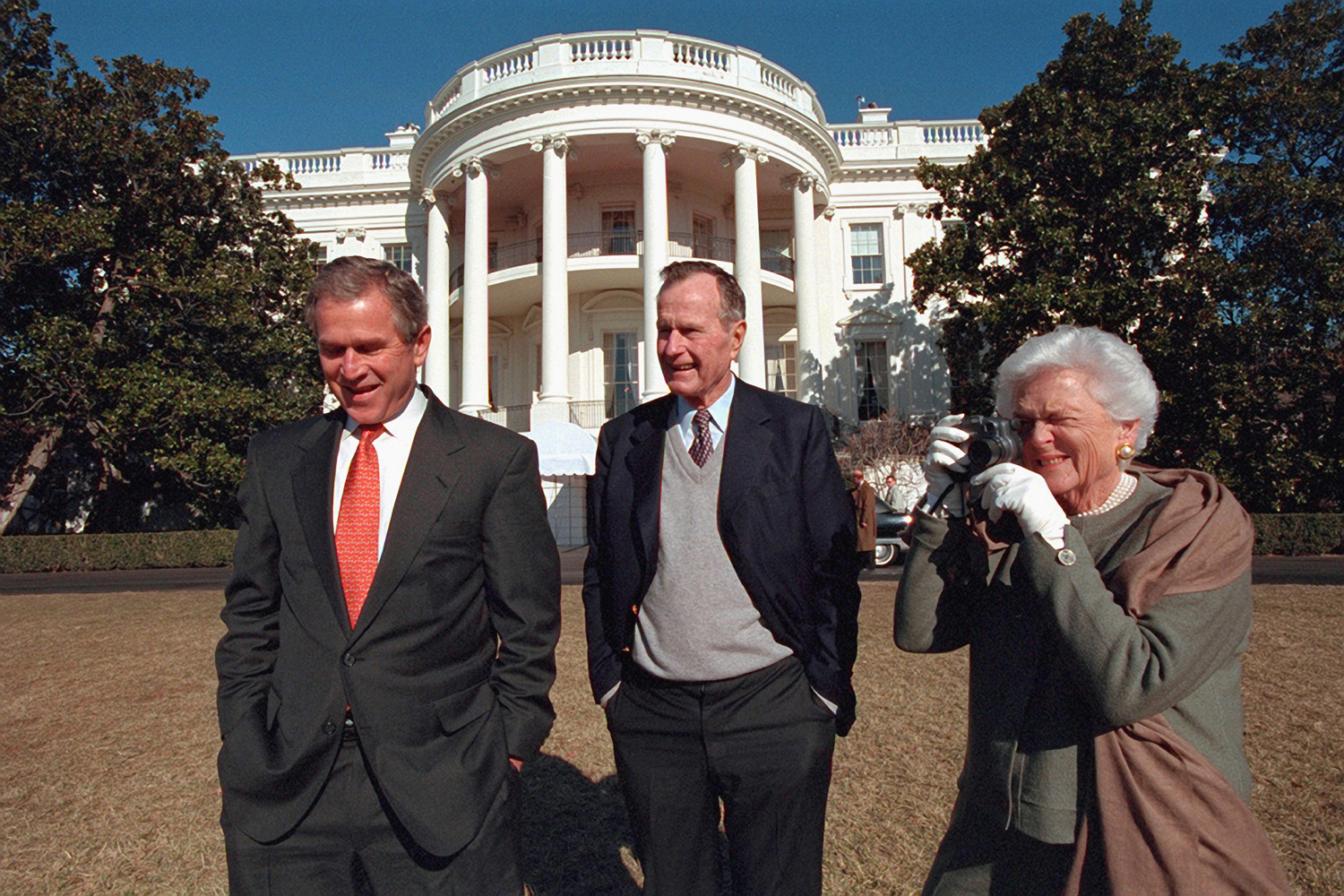 Jan. 28, 2001. The president walks with his parents on the South Lawn of the White House.