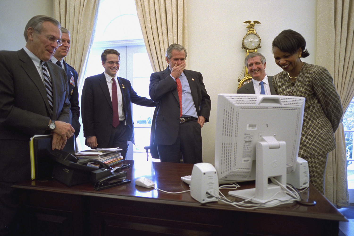 "Feb. 12, 2003. The president watches a Saturday Night Live video on an aide's computer in the Outer Oval Office. Joining him are from left: Secretary of Defense Donald Rumsfeld, General Richard Myers of the Joint Chiefs of Staff, personal aide Blake Gottesman, Chief of Staff Andy Card and National Security Advisor Condoleezza Rice.""He took the presidency seriously but not himself, and always enjoyed a laugh at his expense."""
