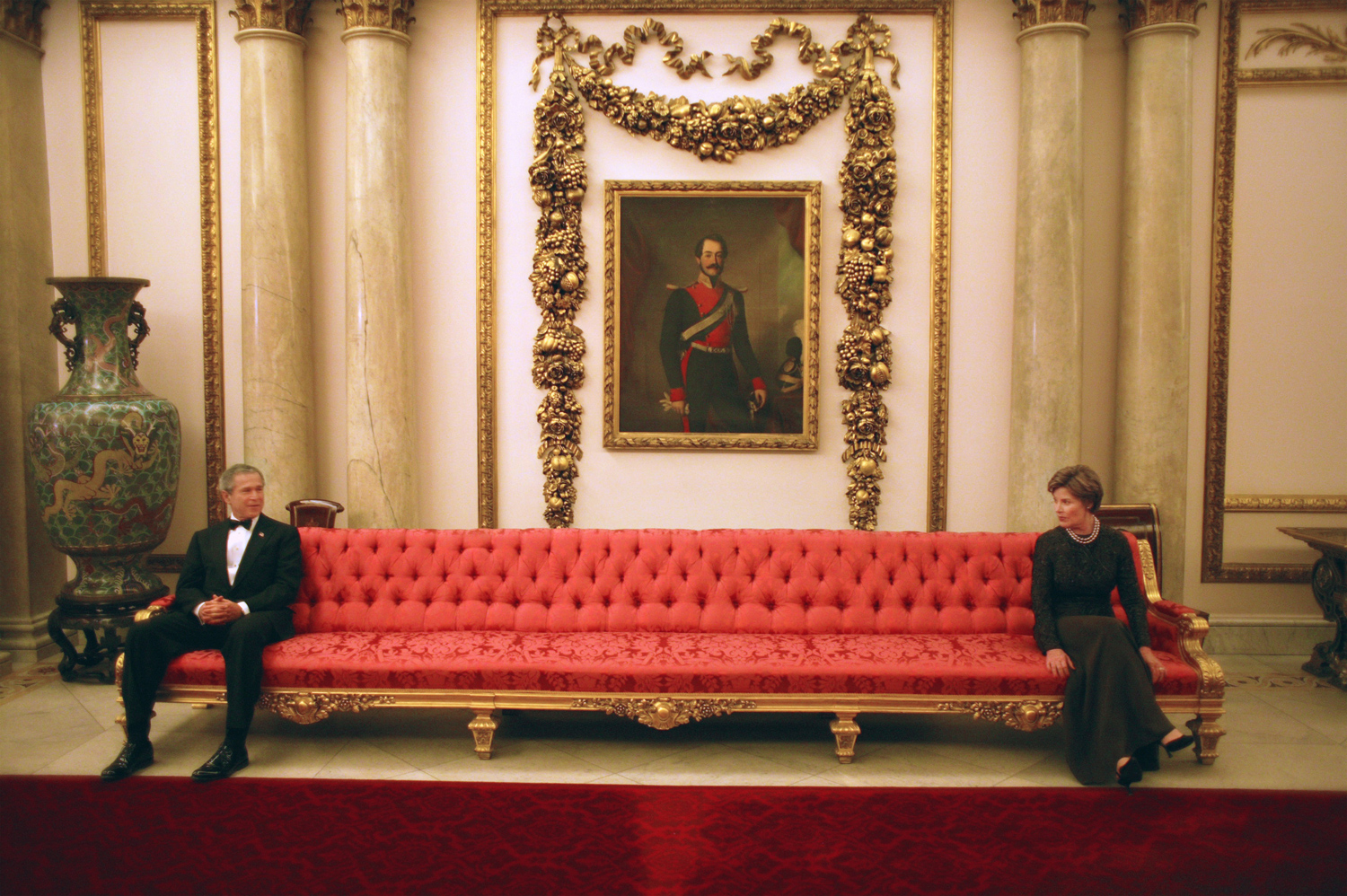 "Nov. 20, 2003. President and Mrs. Bush enjoy the moment as they sit on either ends of a couch prior to a social event at Buckingham Palace.""It was fun to be at Buckingham Palace, and not just for me. The President and Mrs. Bush were like kids on this very long couch, playfully looking at one another from each end."""