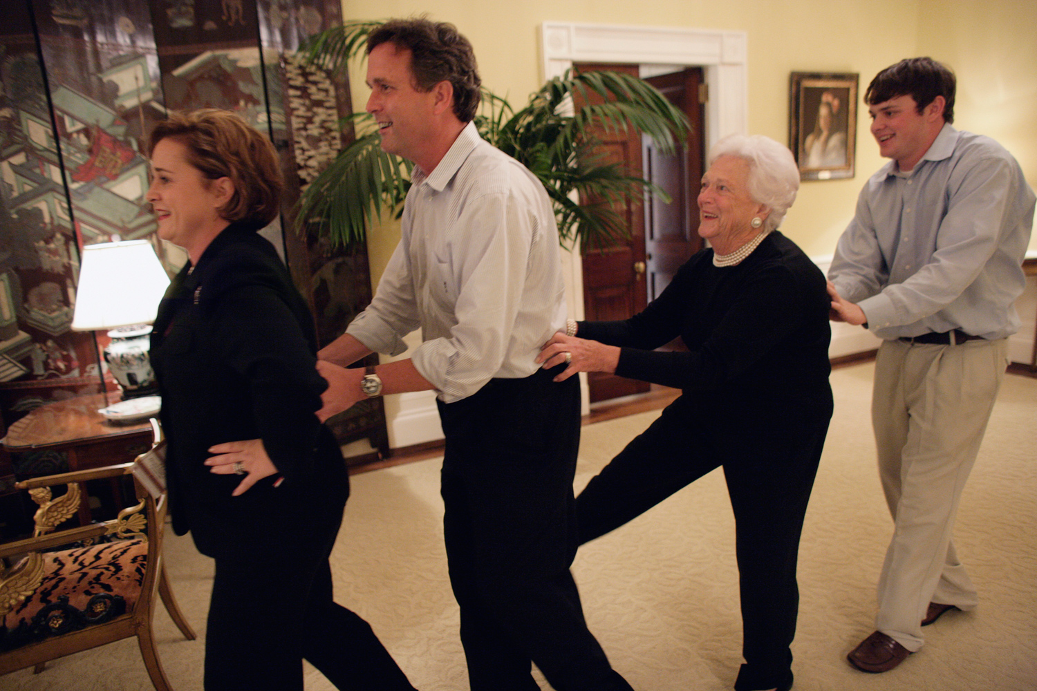 Nov. 3, 2004. Doro Koch leads Marvin Bush, Barbara Bush and Sam LeBlond in a conga line during election night in the Private Residence of the White House.