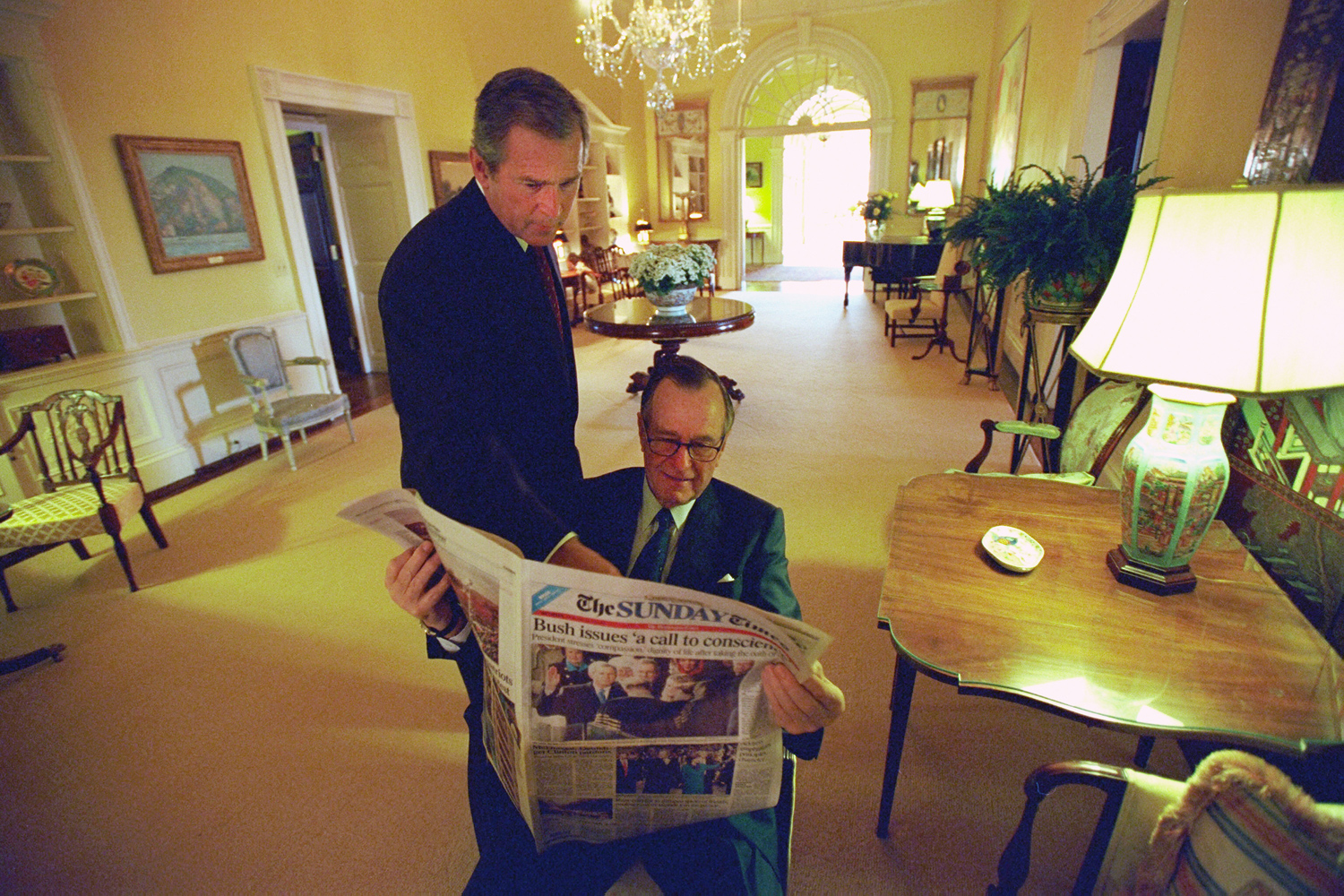 Jan. 21, 2001. As President George W. Bush glances over his shoulder, former President George H. W. Bush reads the Sunday Times in the Private Residence of the White House.