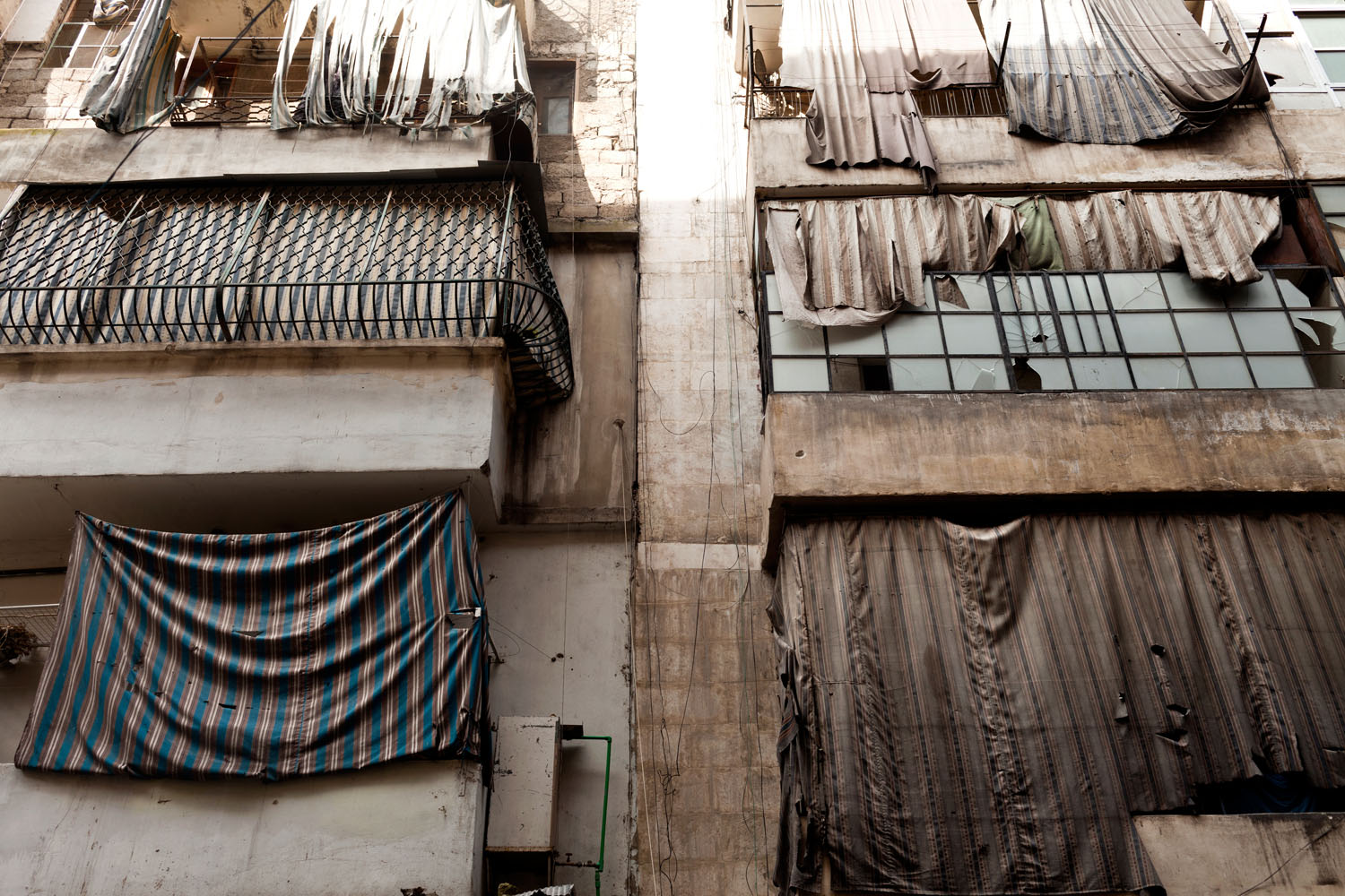 Windows throughout Aleppo are covered in sheets.