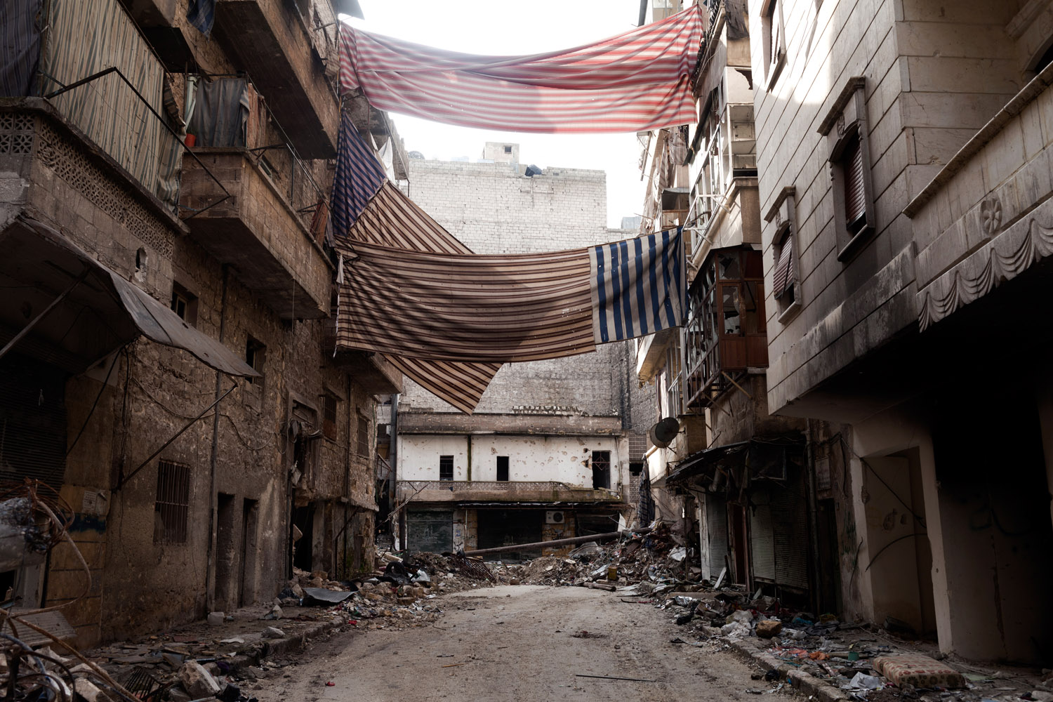 Curtains and drapes, hung along the streets of the Syrian city of Aleppo, act as veils for the city's residents, providing safe passage from the snipers throughout the city.