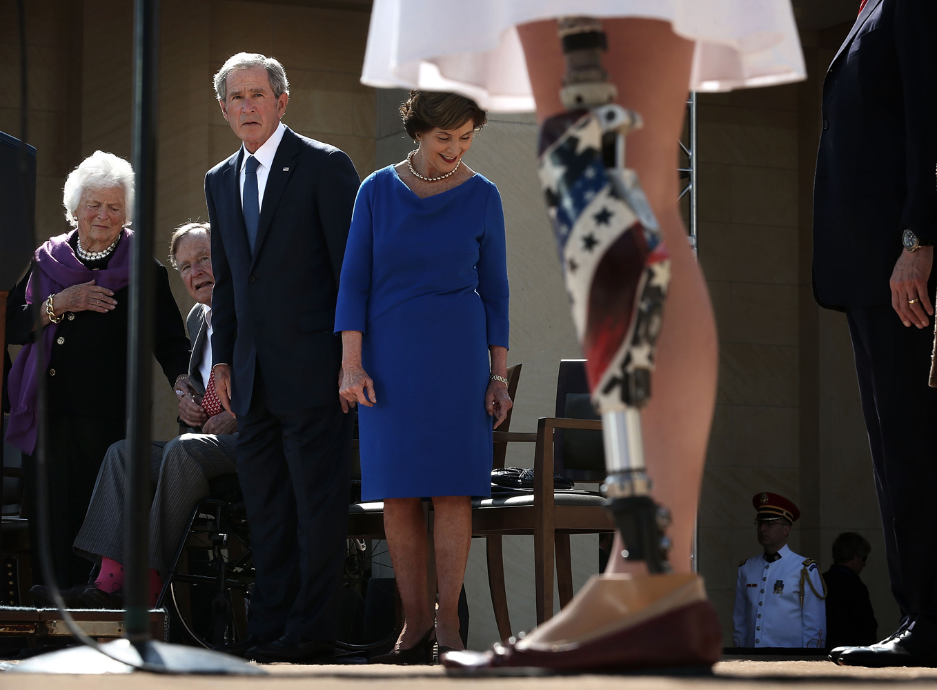 April 25, 2013. Army 1st Lt. Melissa Stockwell (Ret.) (R), who was the first female American soldier to lose a limb in the war in Iraq, recites the Pledge of Allegiance as (L-R) former U.S. first lady Barbara Bush, former President George H.W. Bush, former President George W. Bush and former first lady Laura Bush look on during the opening ceremony of the George W. Bush Presidential Center in Dallas, Texas.