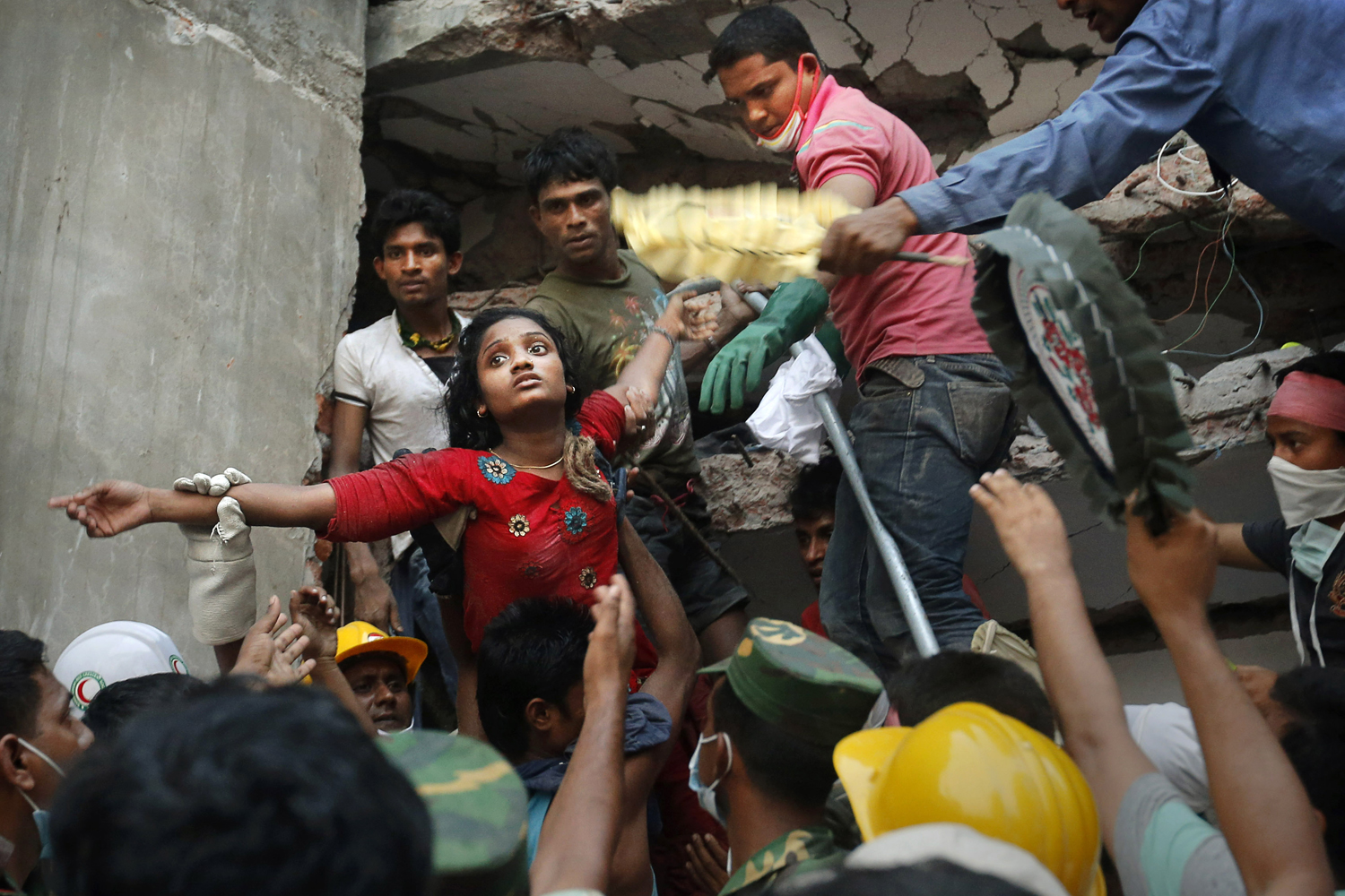 April 25, 2013. A Bangladeshi woman survivor is lifted out of the rubble by rescuers at the site of a building that collapsed in Savar, near Dhaka.