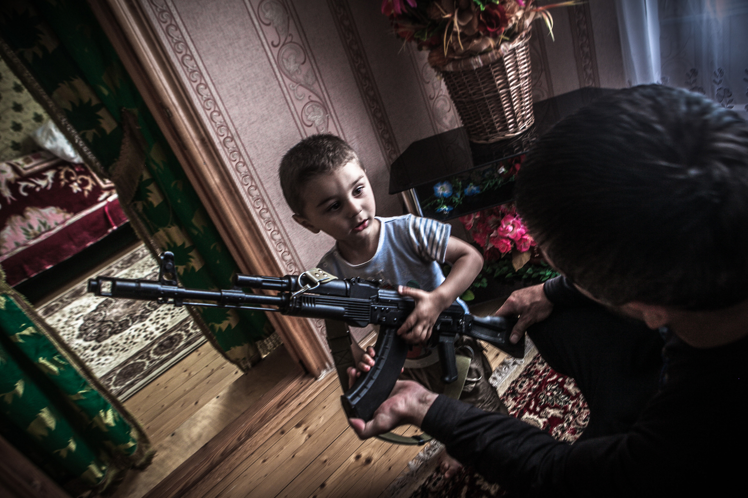 Magomed, a school teacher,  shows to his 2-year-old nephew how to hold a weapon. Dagestan is the biggest and the most multinational republic in the North Caucasus region. The society is mostly based on tradition and still is very conservative.